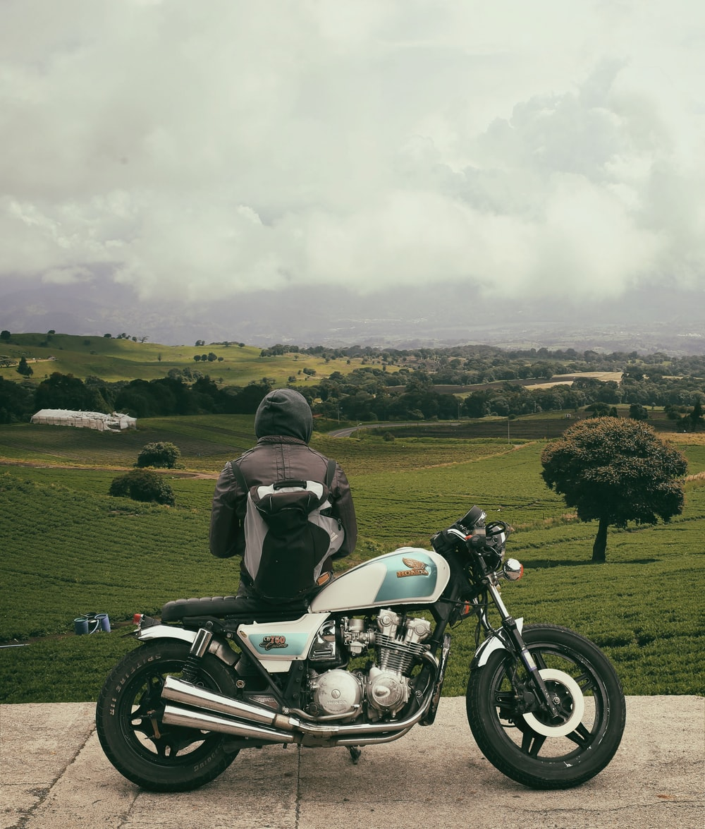 man sitting on motorcycle while facing broad green field