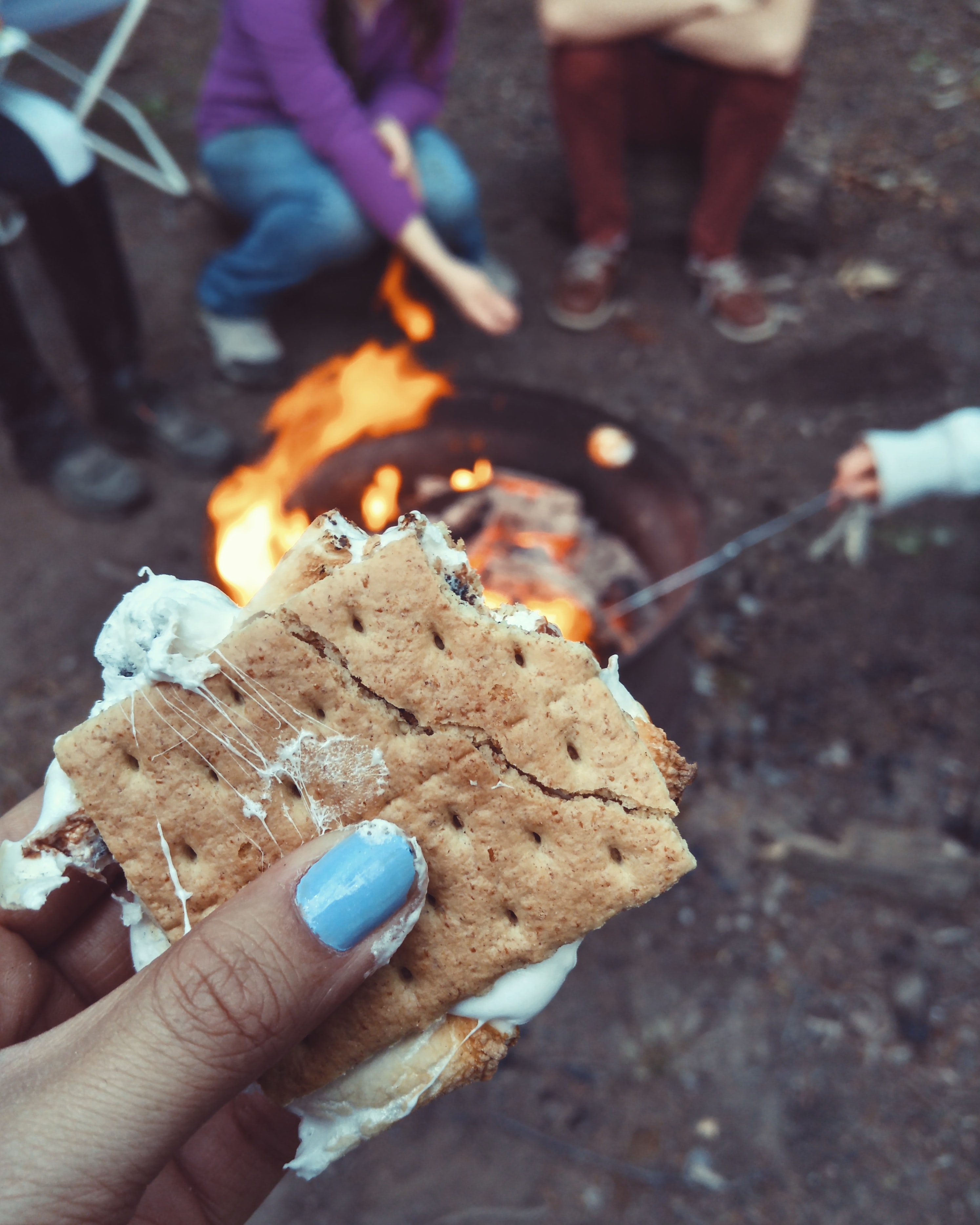 Close-up of the hand of a woman holding a piece of S'more at a campfire.
