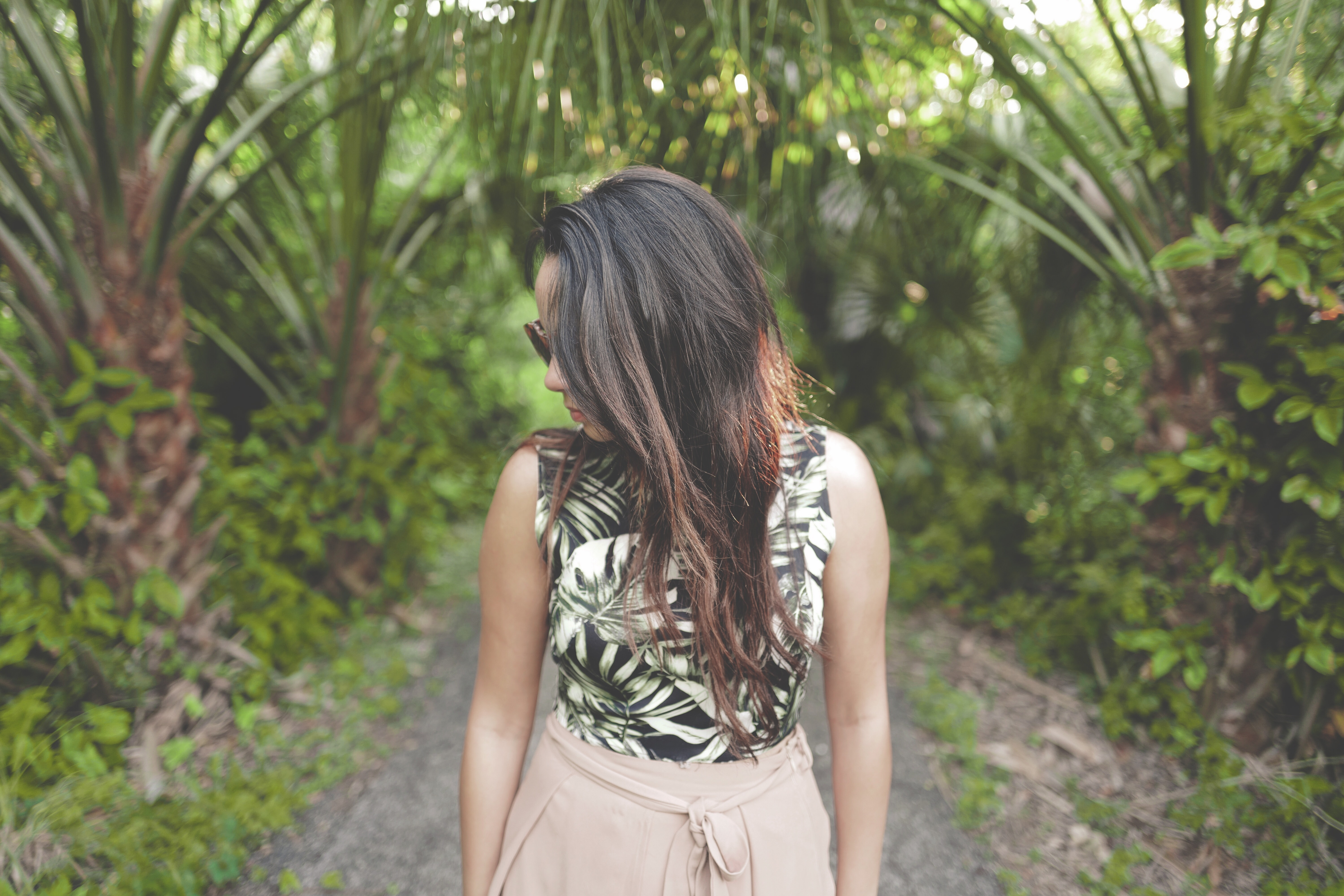 A young dark-haired woman in sunglasses tilting her head to the side in a tropical setting