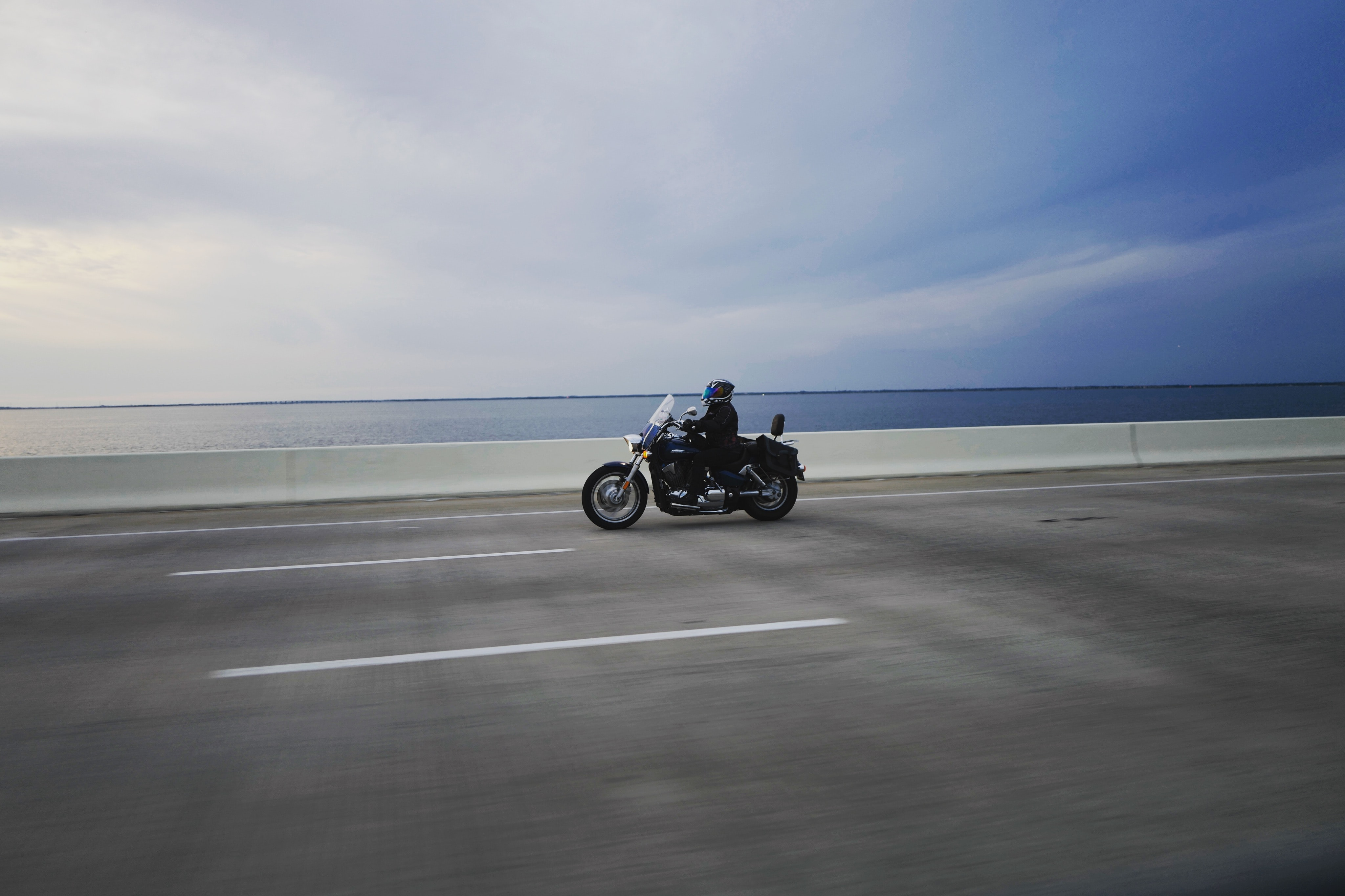 A person on a powerful motorcycle driving on a bridge with water stretching to the horizon