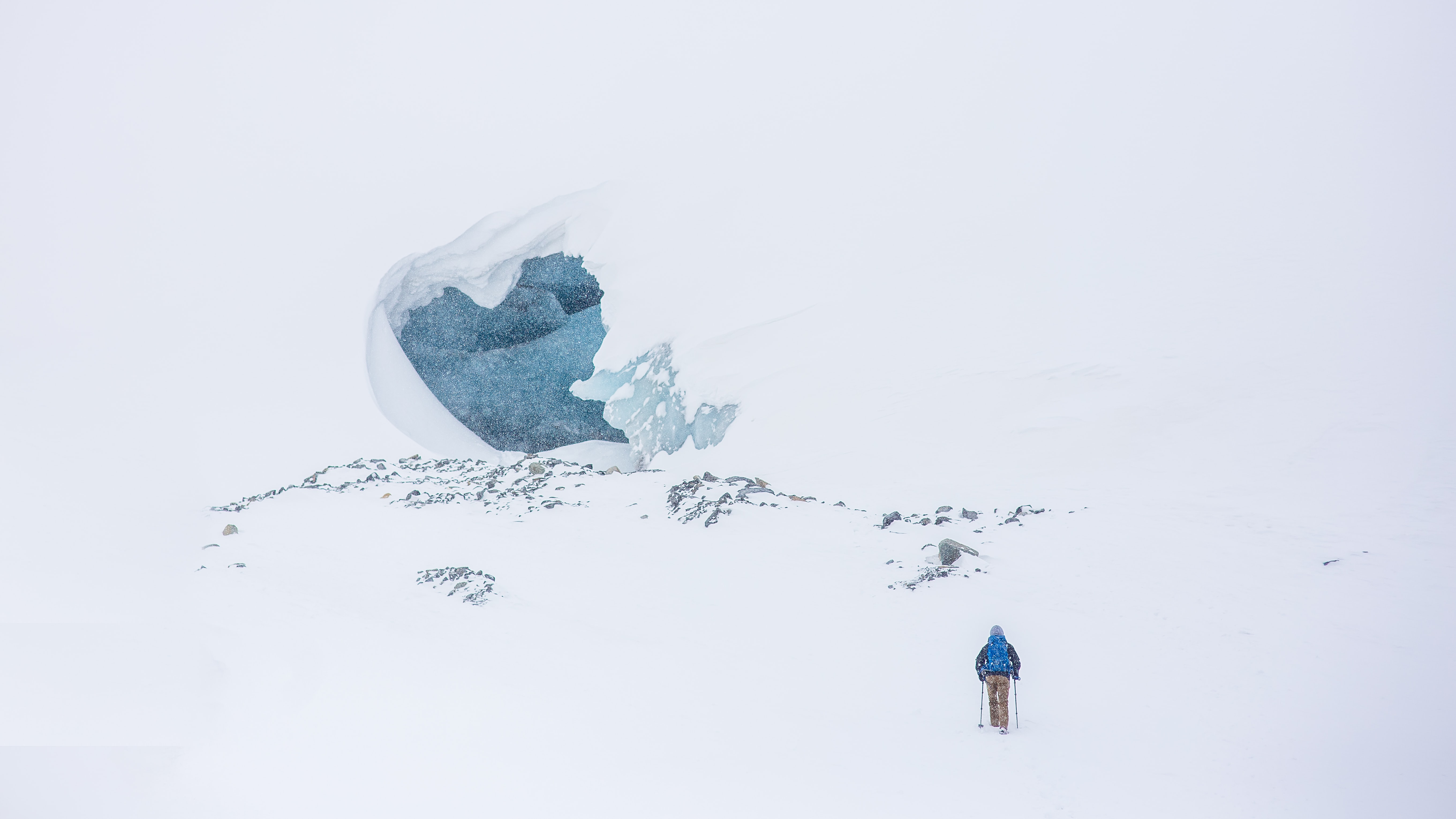 A landscape of a hiker walking in the snow to a ice cave