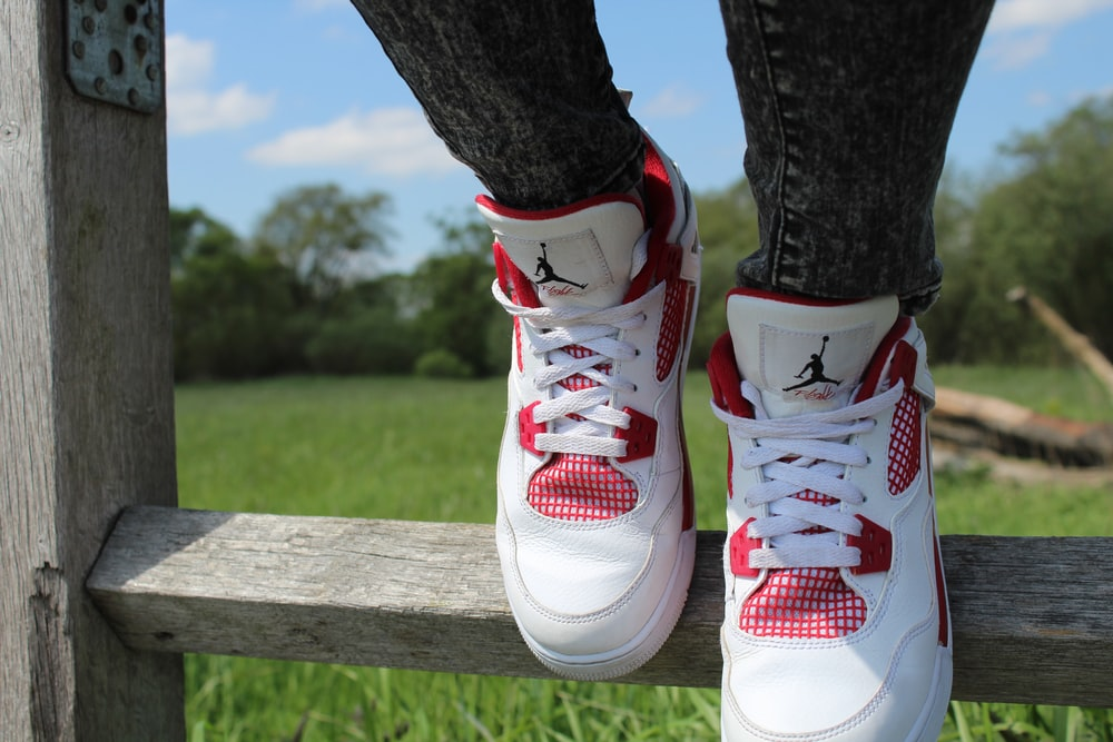 person wearing pair of red-and-white Air Jordan shoes