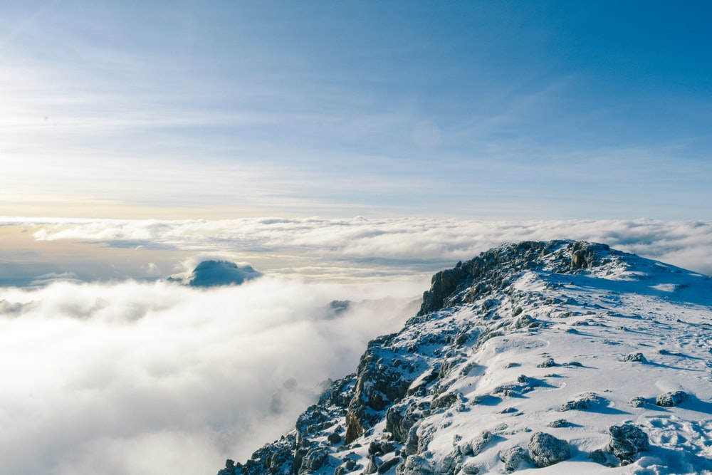 mountain covered by snow near sea of clouds