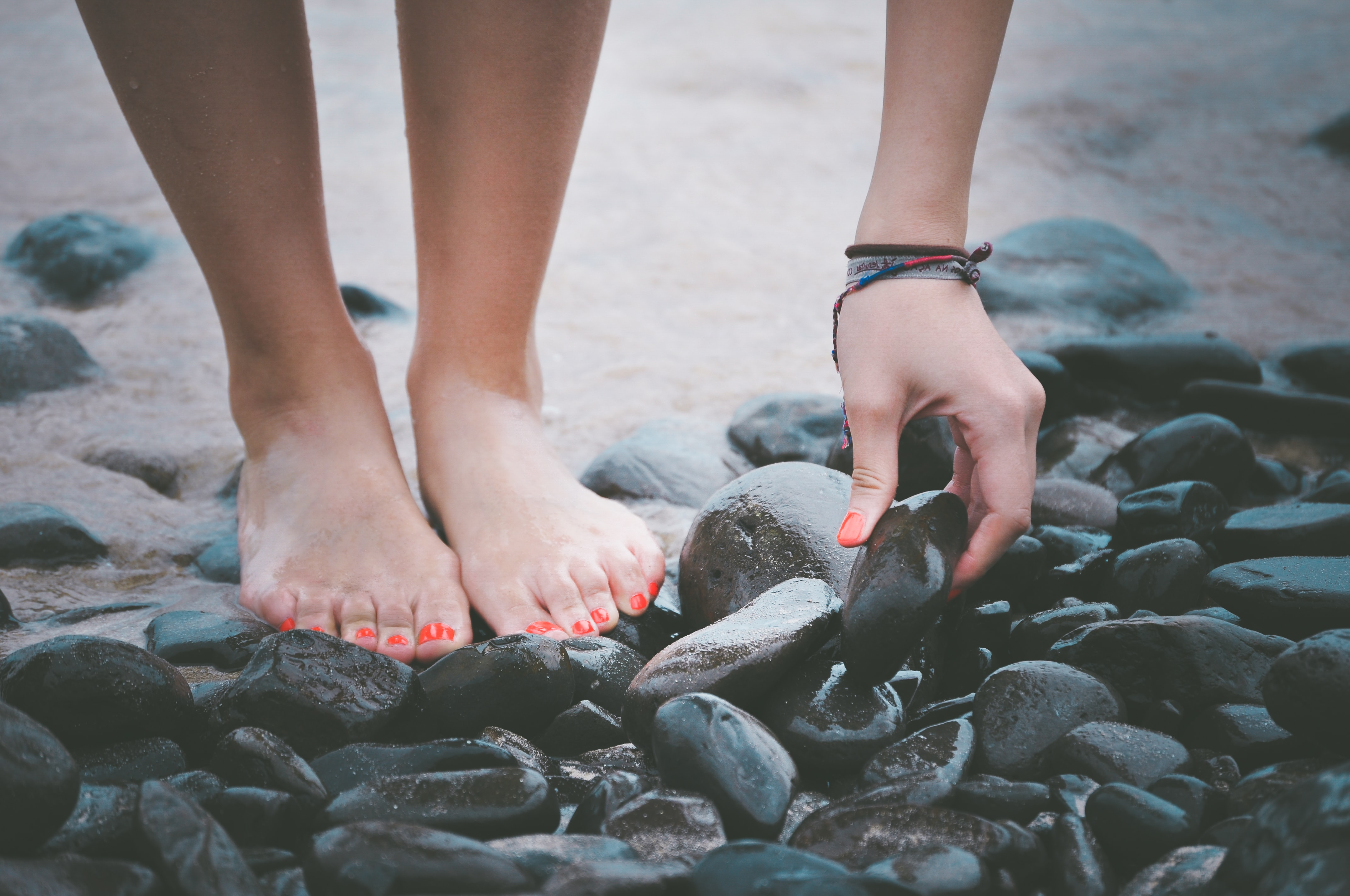 A low shot of a woman standing on wet pebbles and picking up one of them