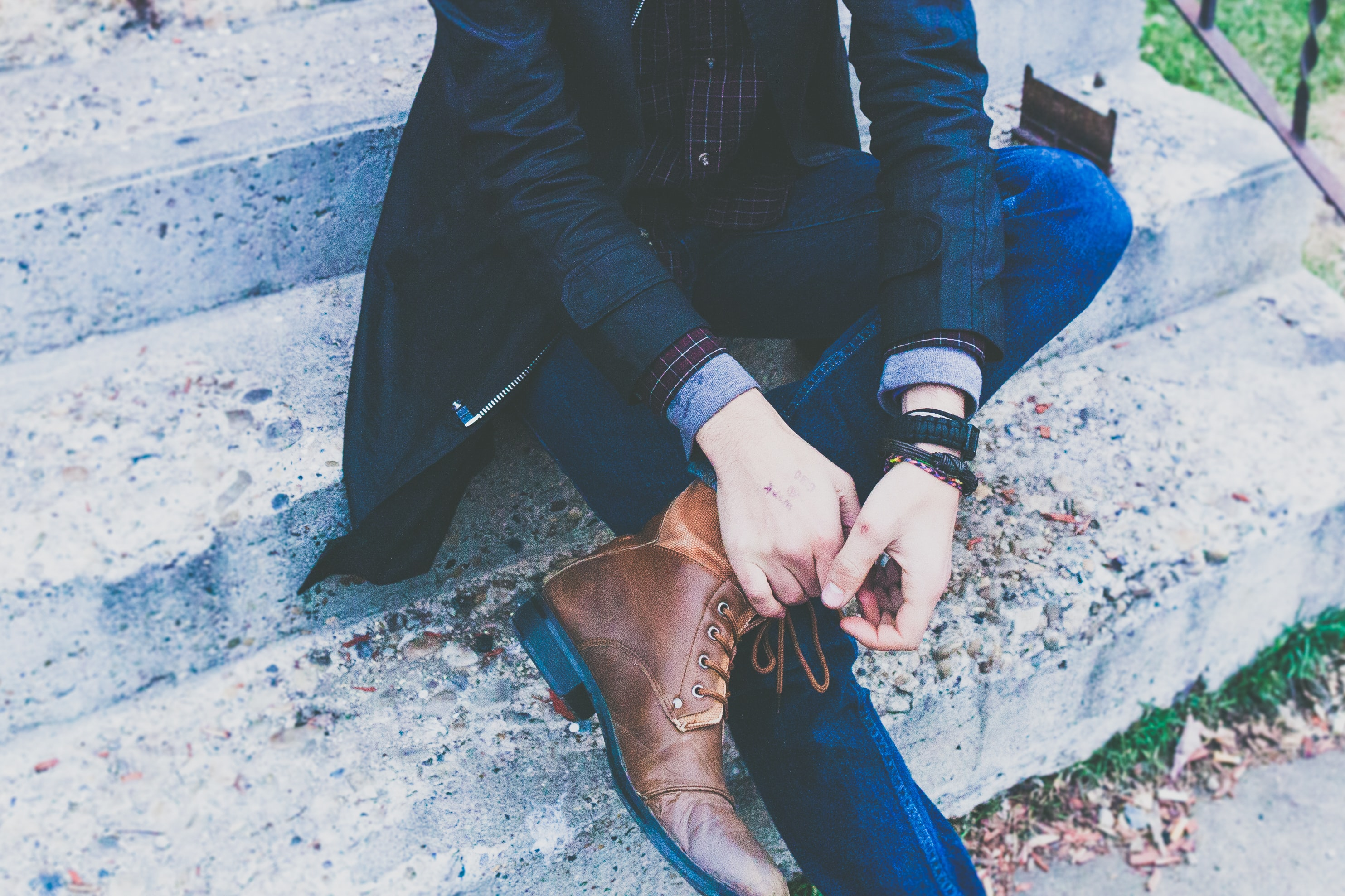 A man in an elegant jacket and jeans tying his leather shoes while sitting on stairs