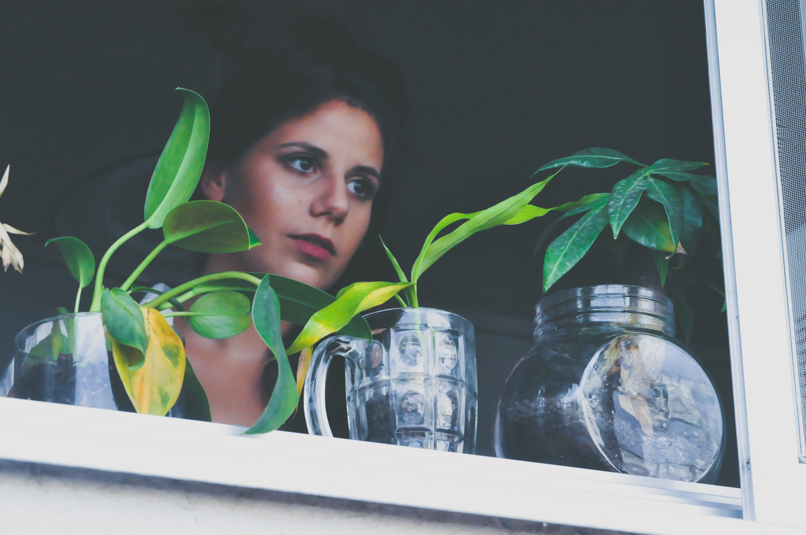 A woman staring out a window with plants on the sill.