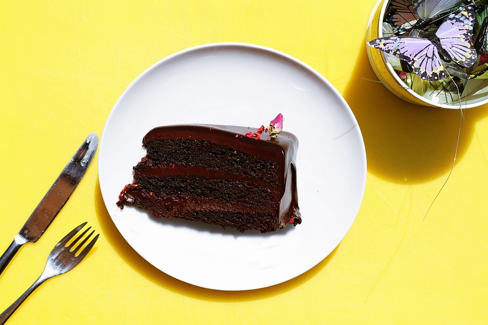 sliced chocolate moist cake in plate near gray stainless steel fork and knife