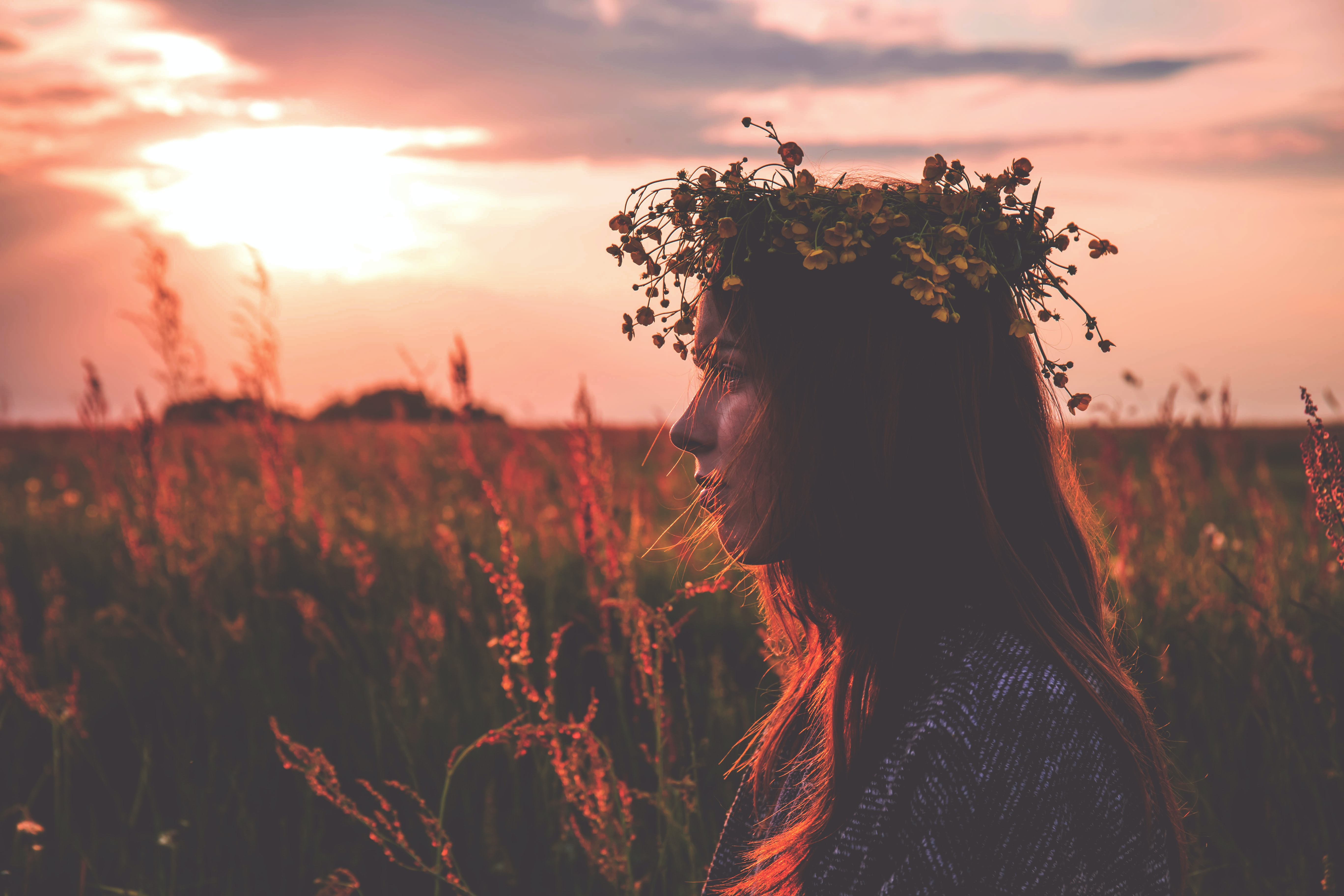 Young Bohemian girl with flower crown poses in meadow with light from sunrise at Suchawa