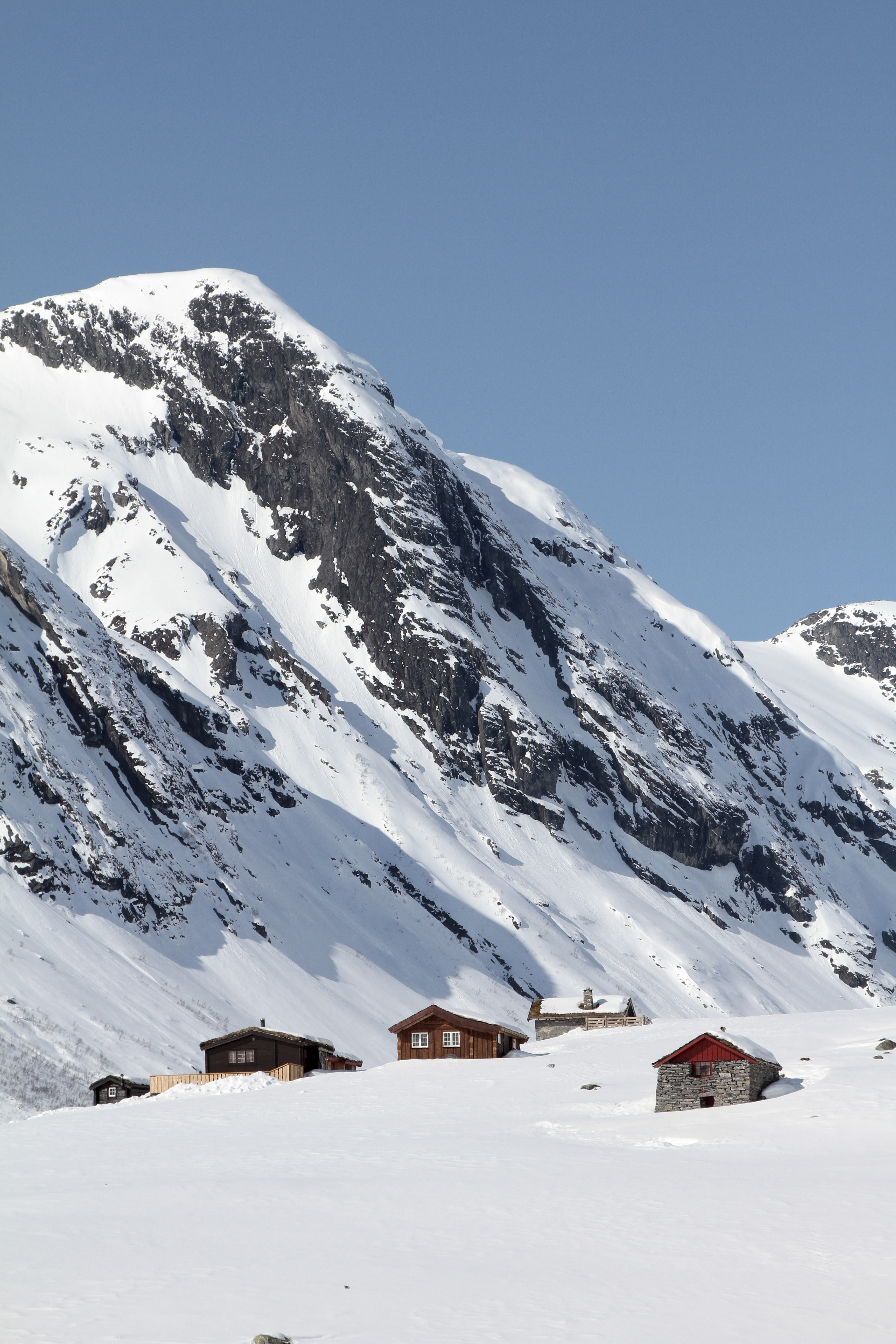 Houses at the top of a hill with snow capped mountains in the background and blue skies