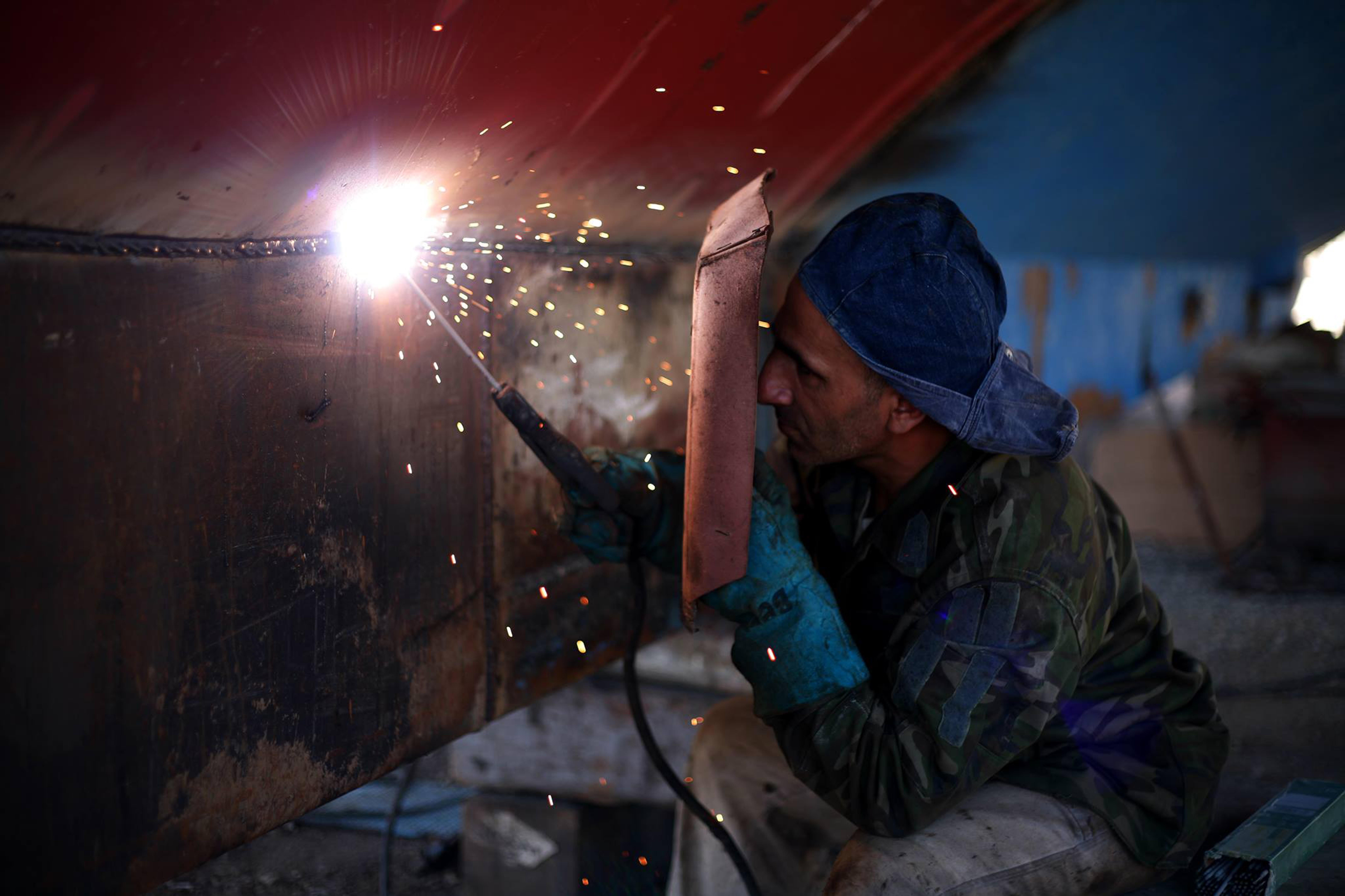 man welding the brown metal board