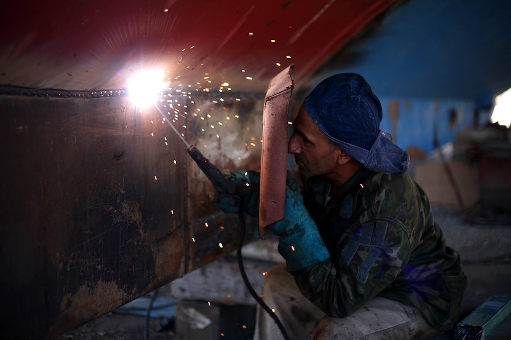 man welding the brown metal board