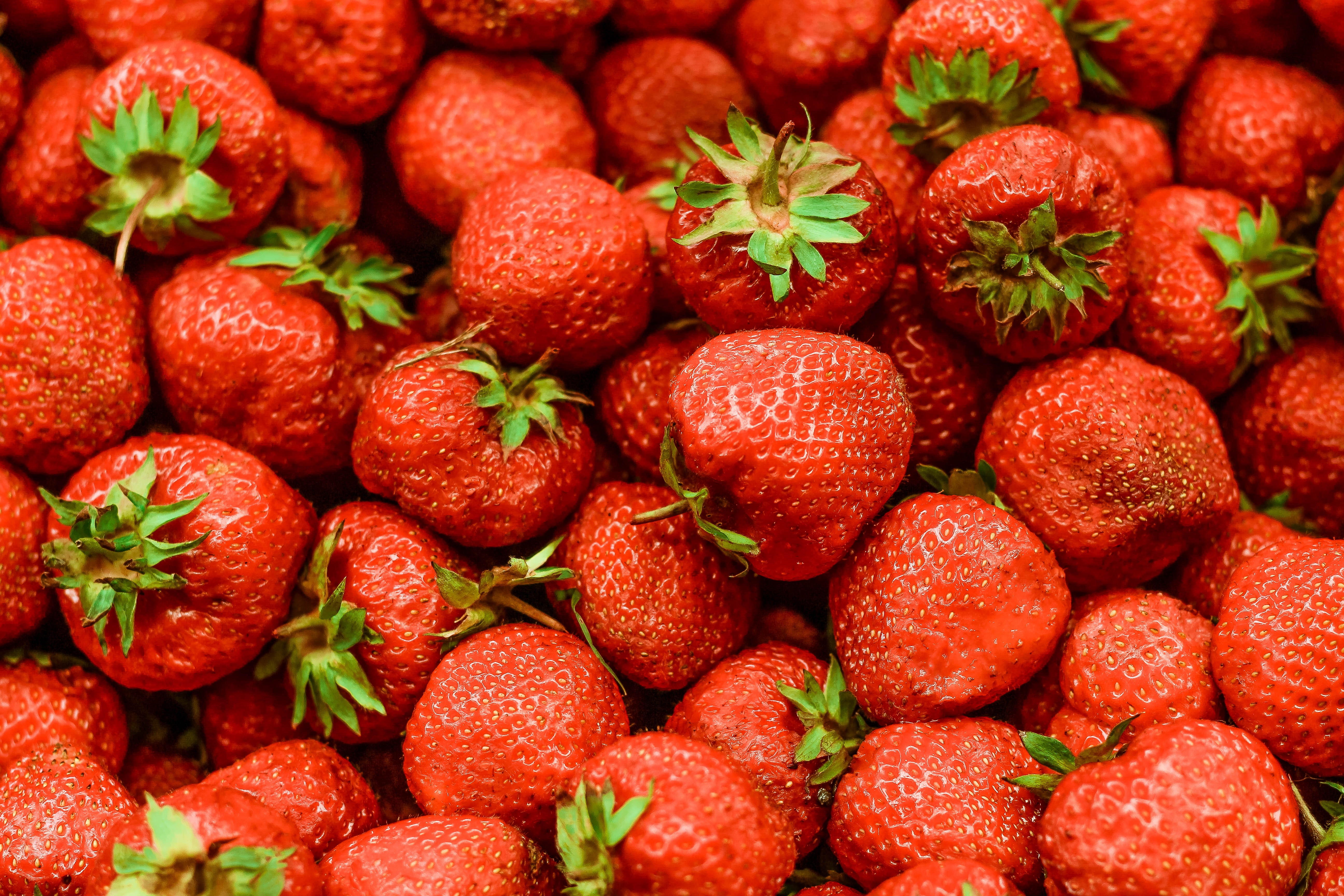 Pile of fresh strawberries with green tops
