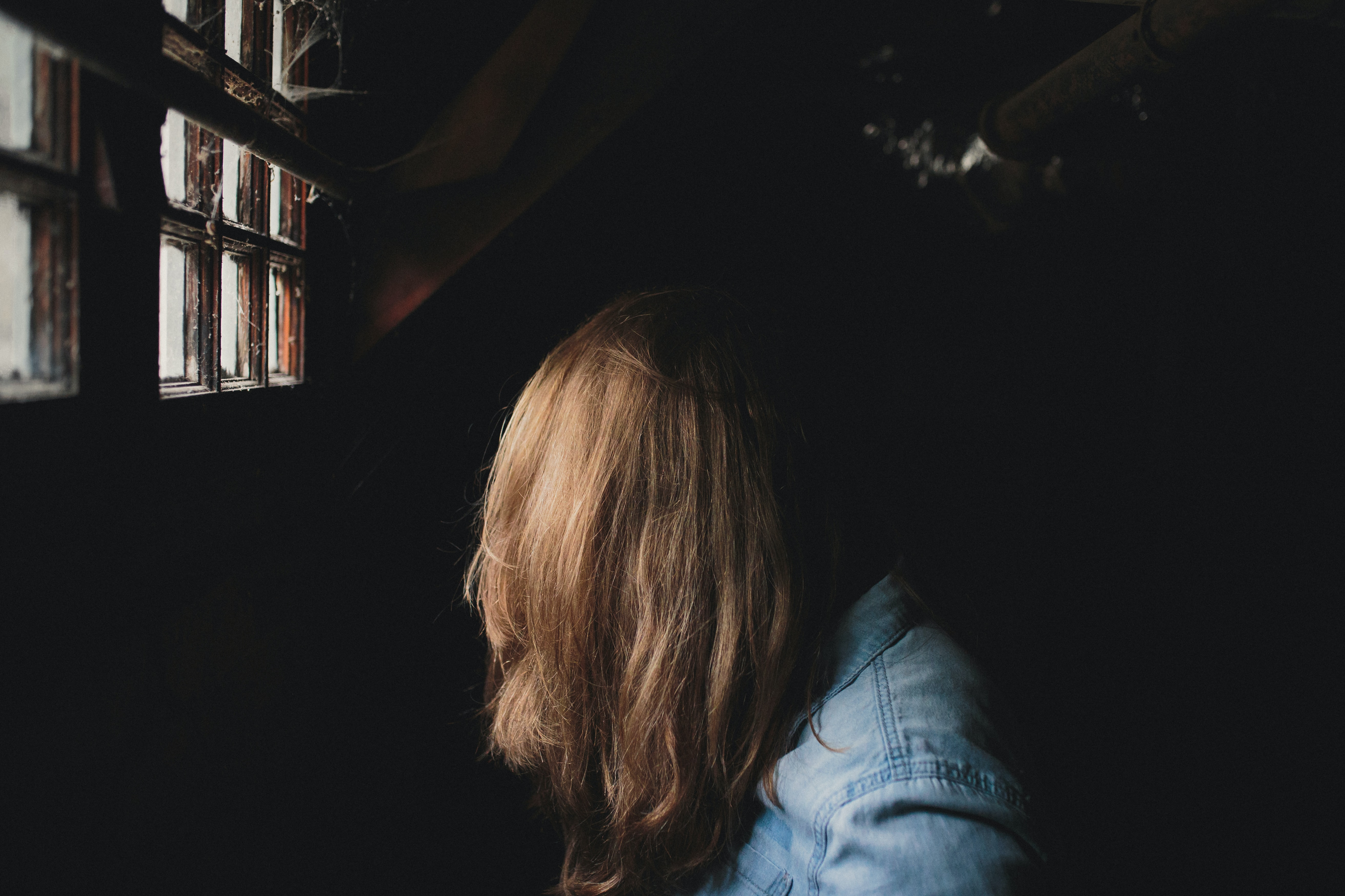A female sitting sideways in a denim jacket has long blonde hair obscuring her face