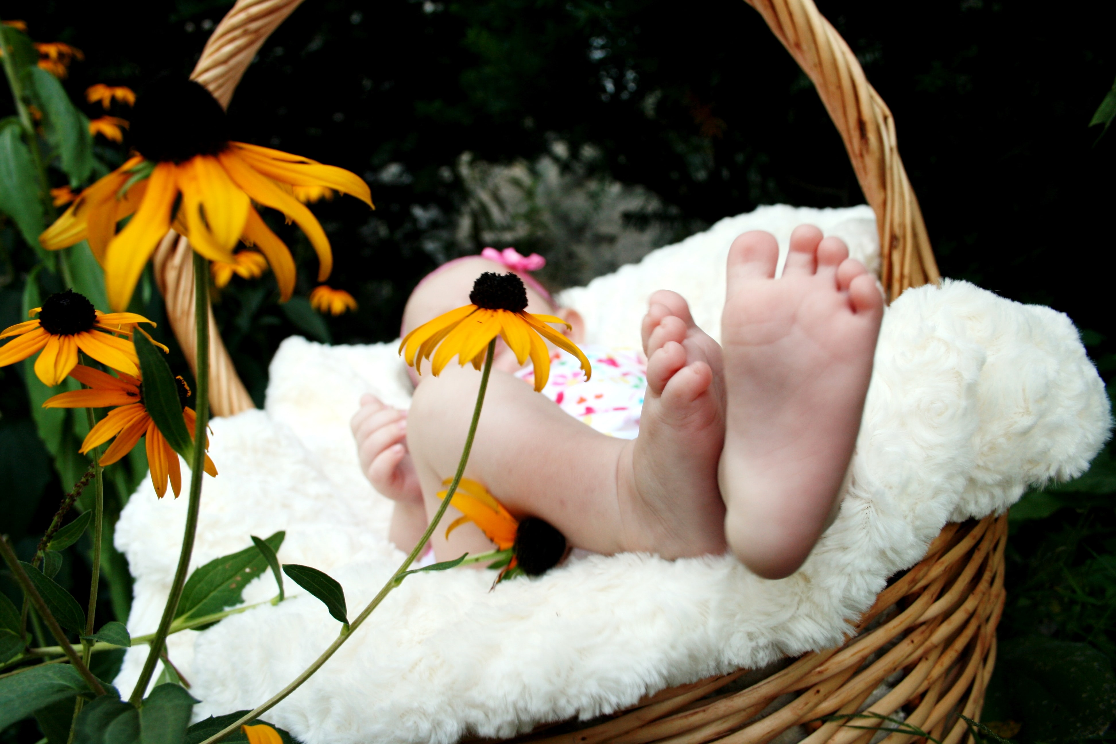 A barefoot baby on a soft blanket in a wicker basket