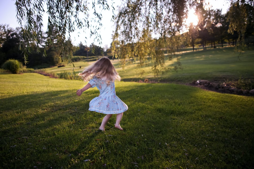 girl dancing on green grass field