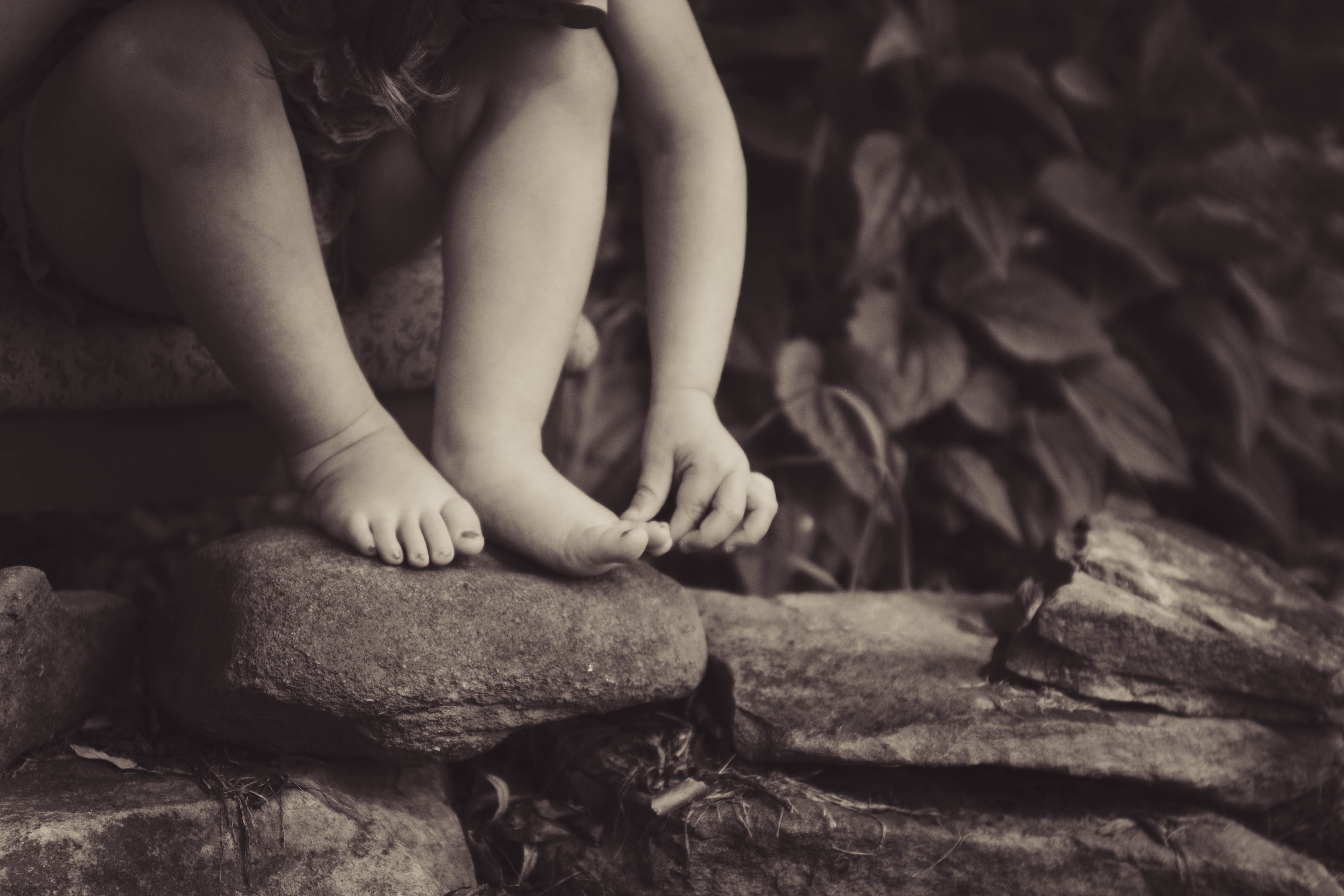 depth photography of child sitting on rock beside plant