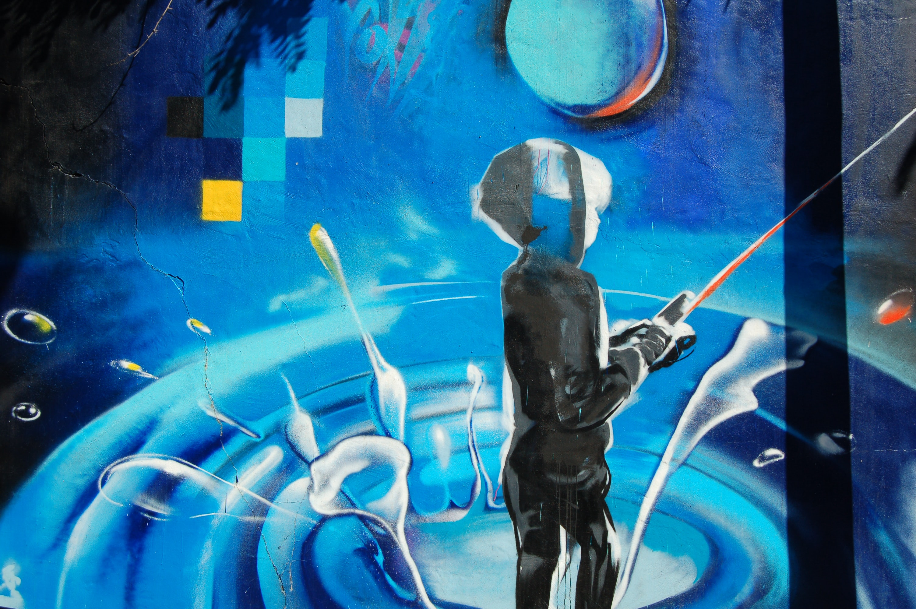 A wall mural of a person in a hooded jacket standing in water fishing.