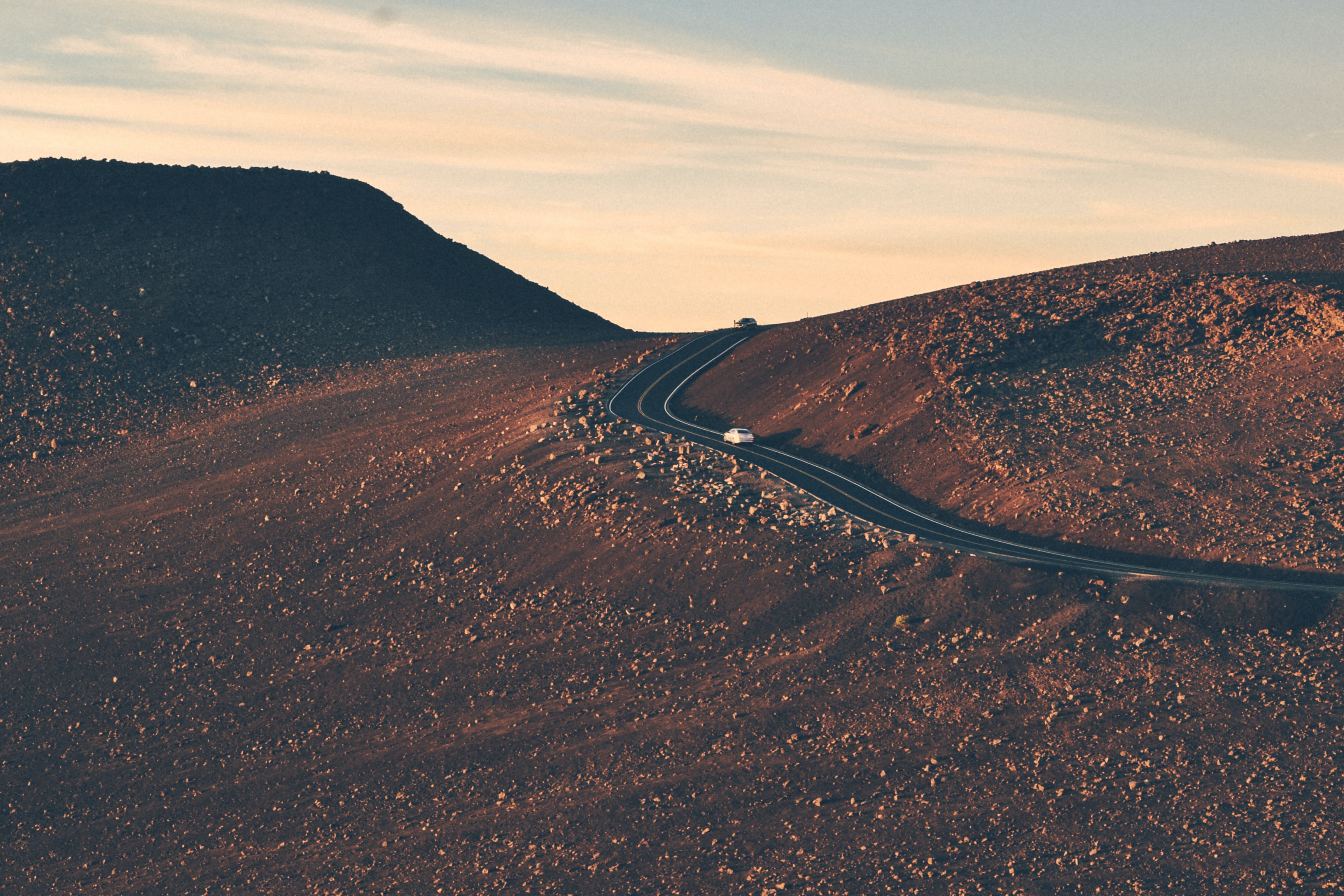 Two cars driving up an asphalt road on a slope covered with small rocks during sunset