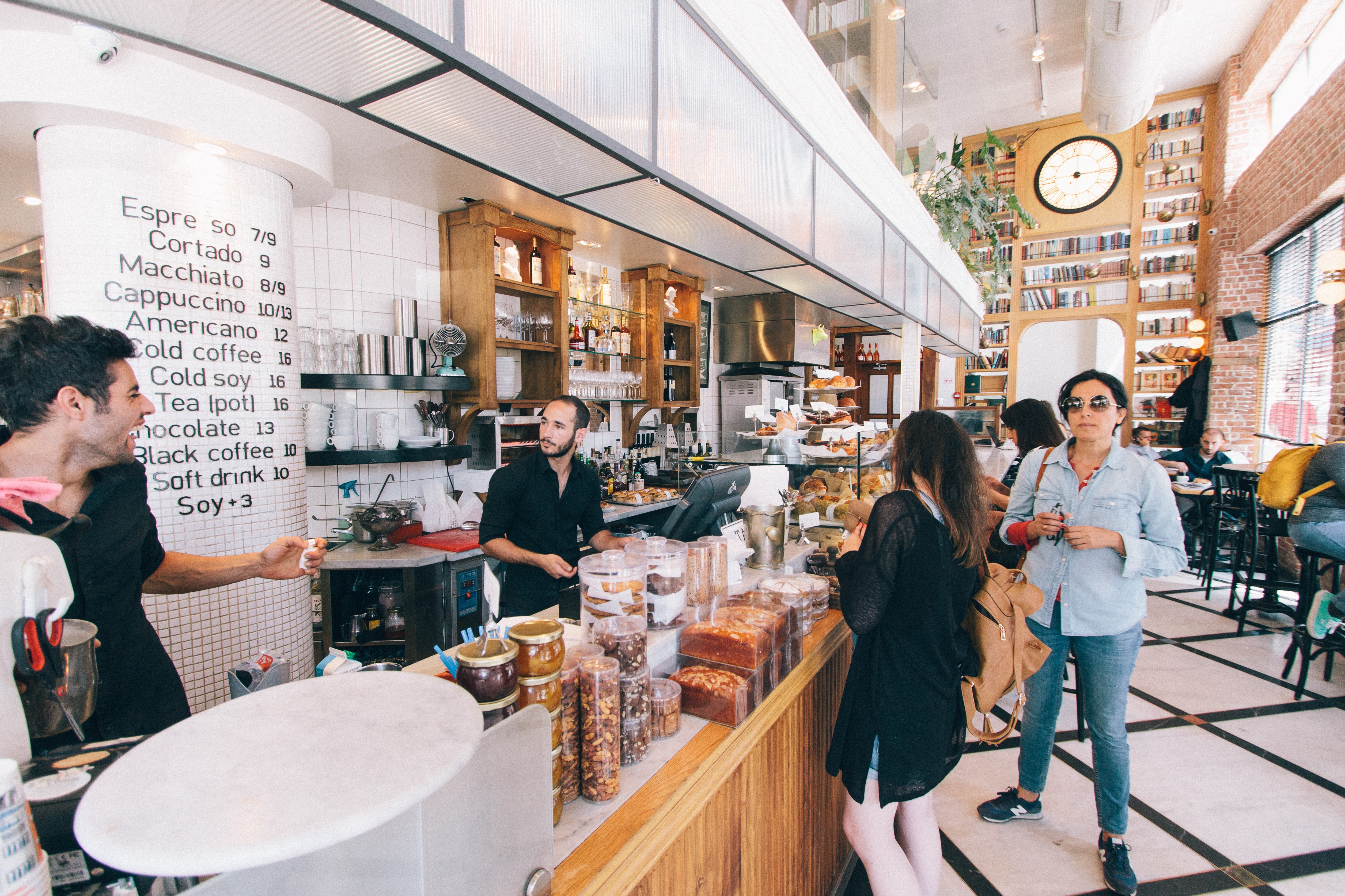 Customers and baristas near the counter in an elegant coffee shop in Tel Aviv