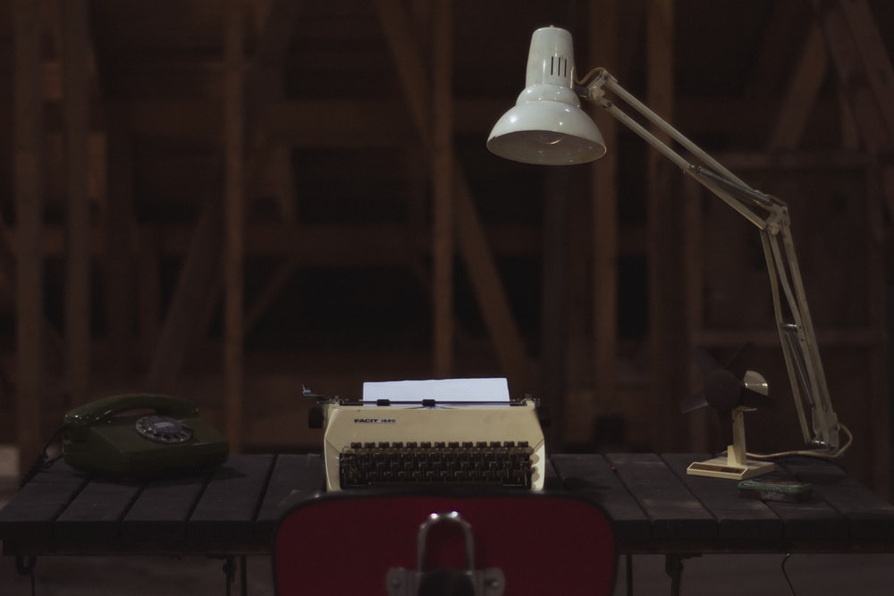 white and black type writer beside telephone on top of brown table