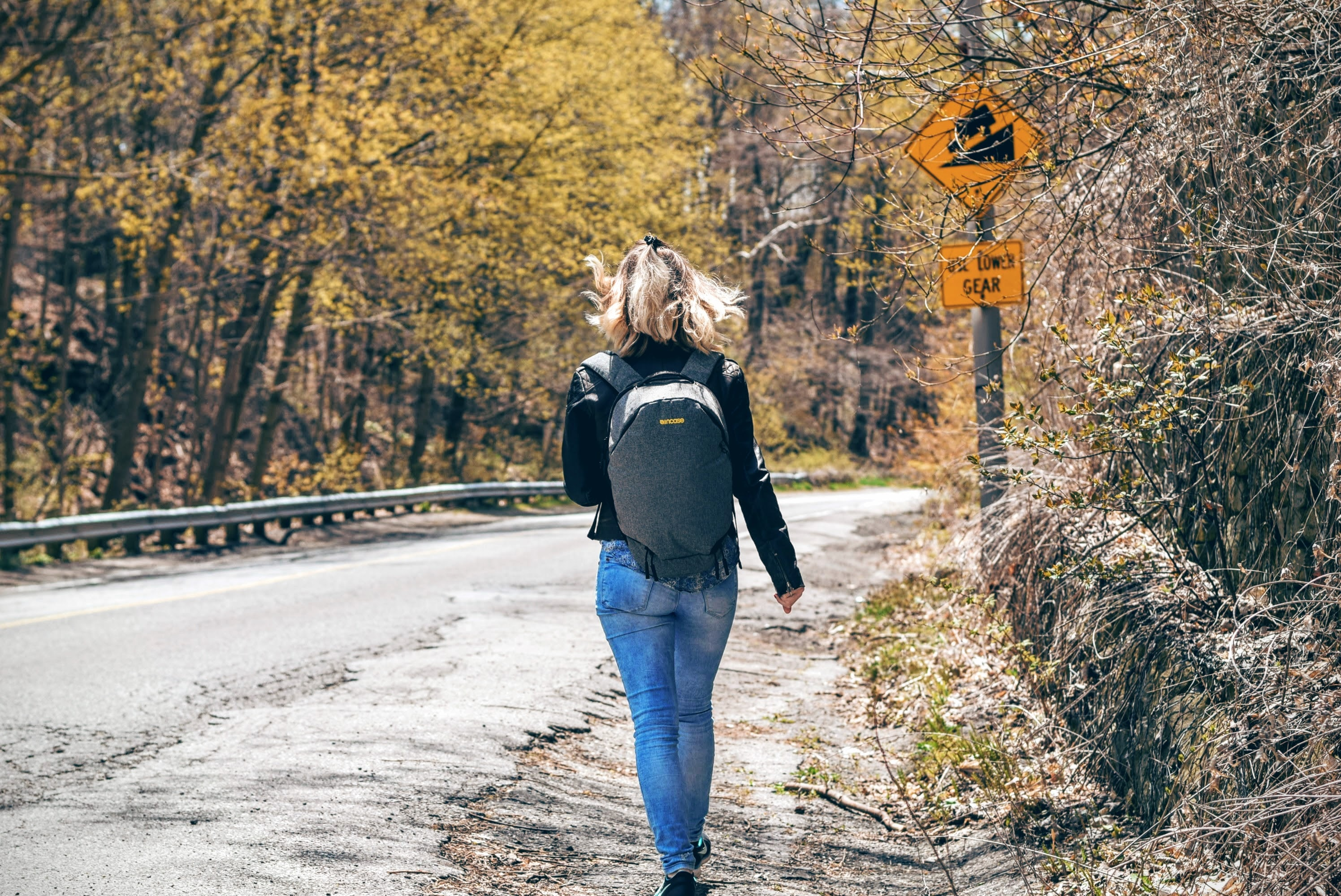Woman walks along a windy rural road wearing a backpack