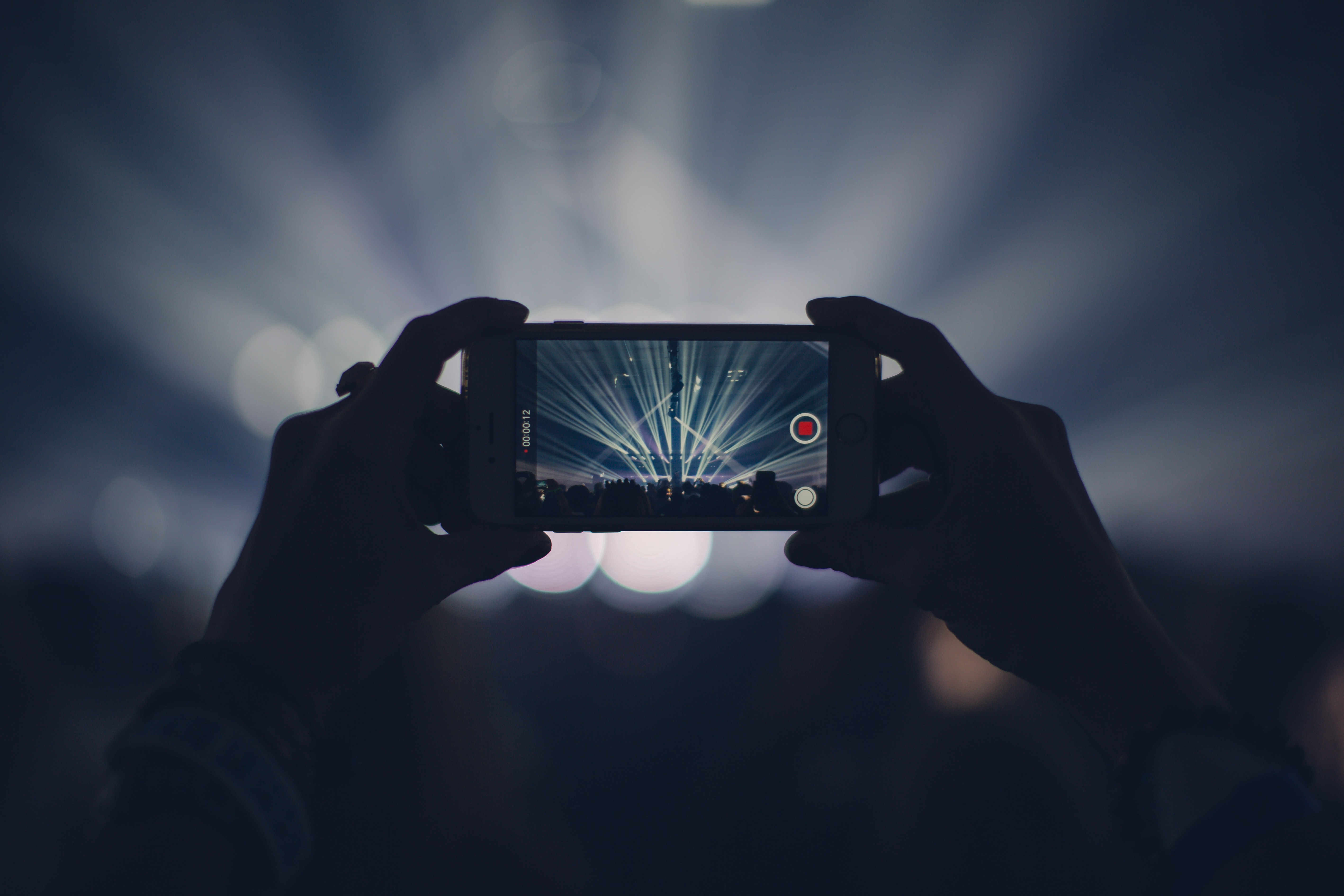 person taking video of live concert