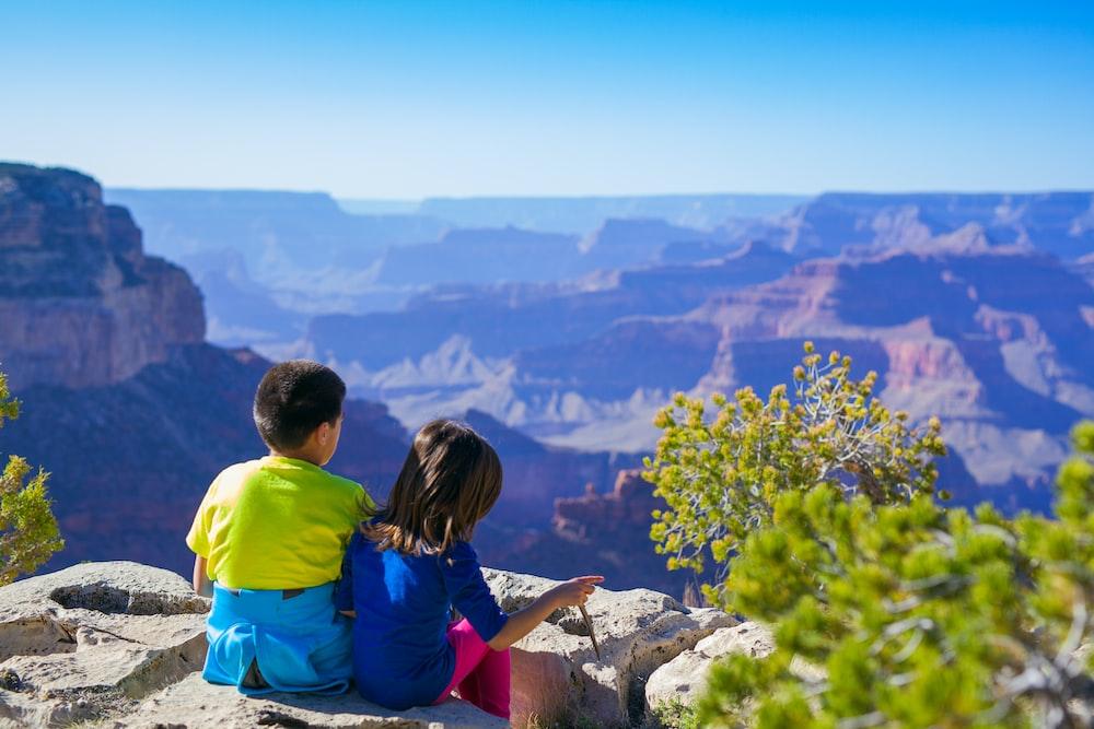 boy sitting beside girl in blue shirt near green leafed tree