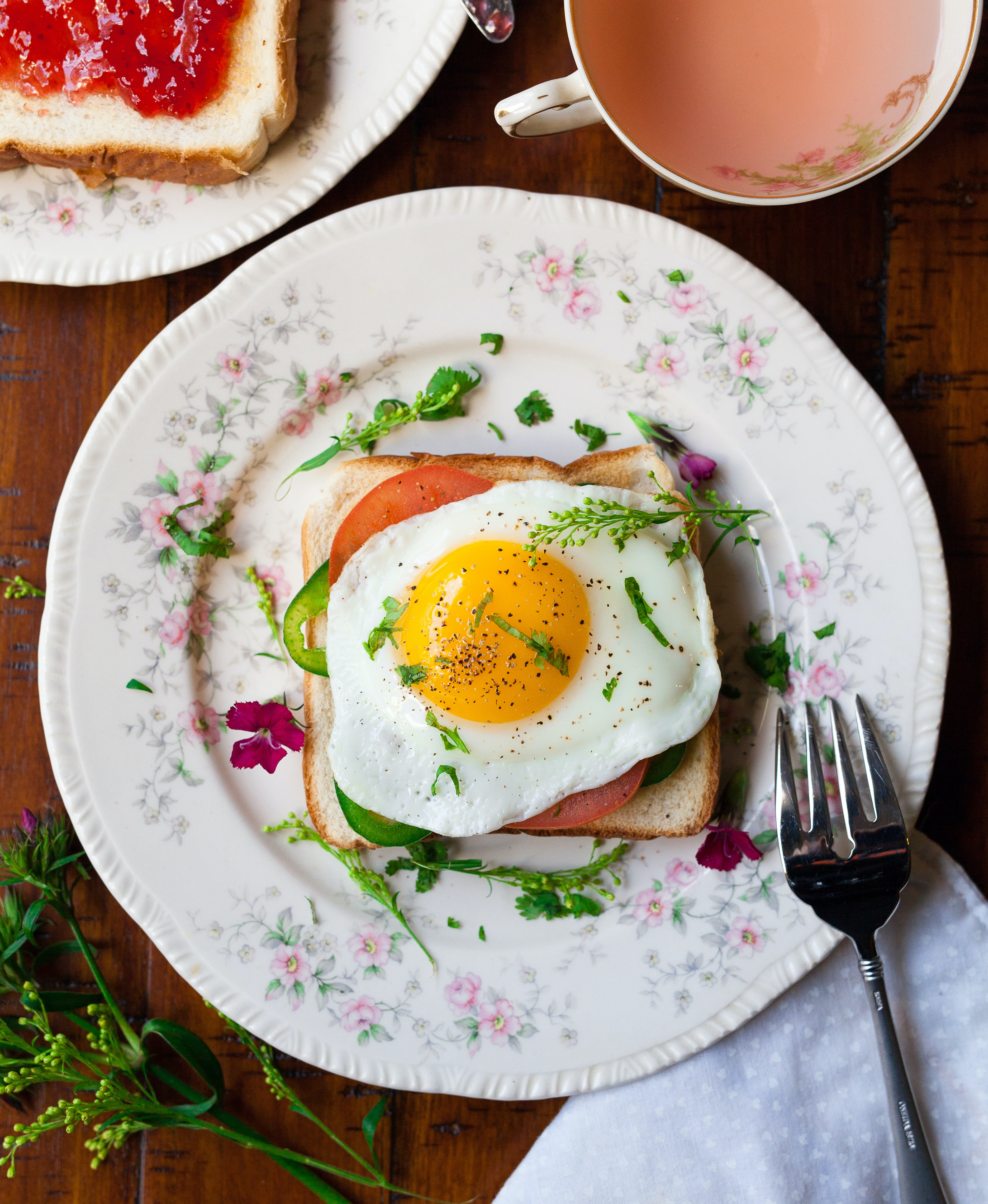 Breakfast toast with fried egg, tomato, and herbs