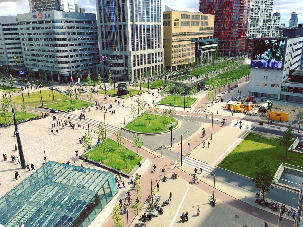 aerial photography of people walking on park near city buildings