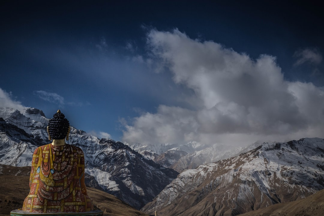 Sitting buddha overlooking open mountains and land with clouds above