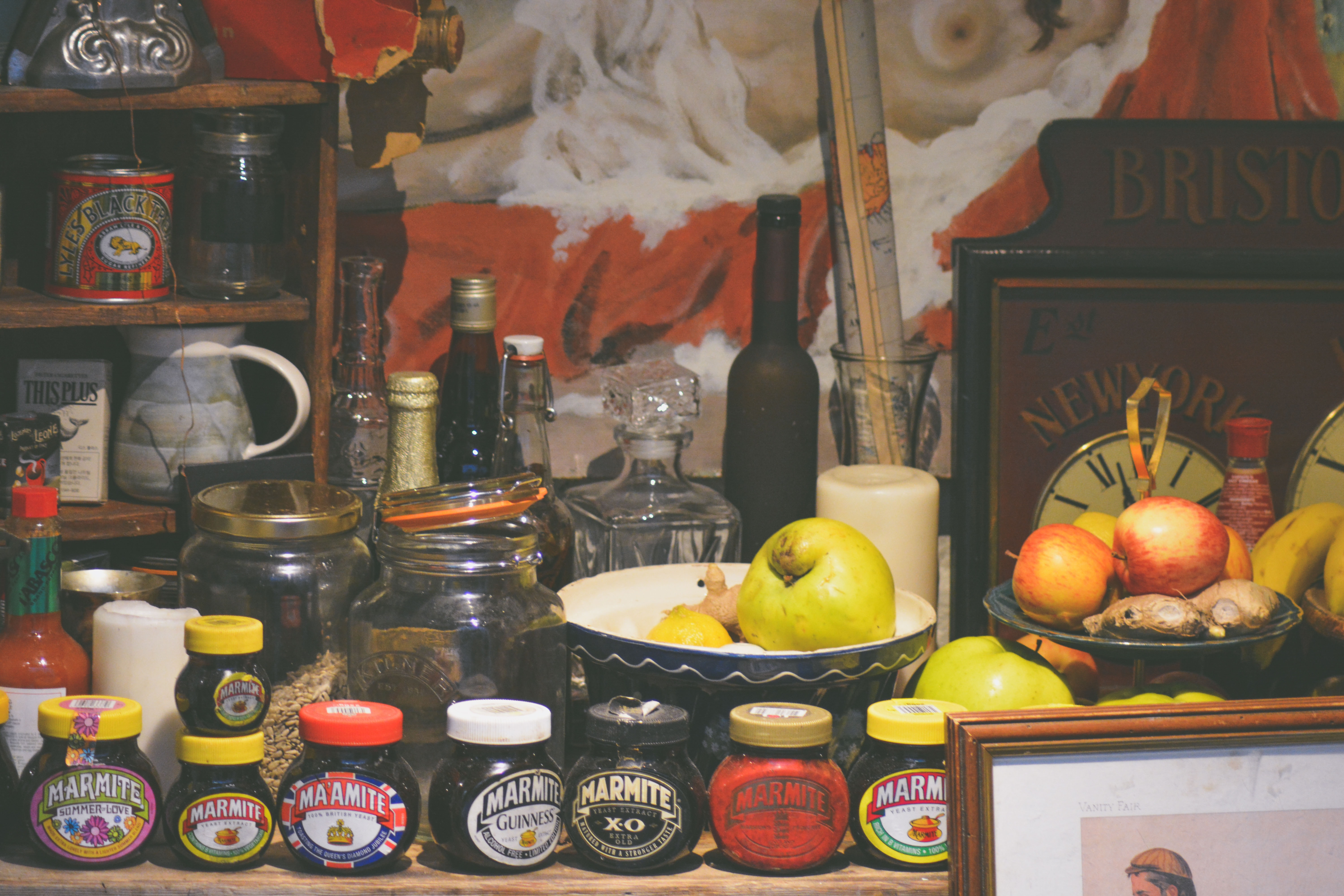 A busy shelf with a row of Marmite jars, fruit bowls, empty jars and wine bottles