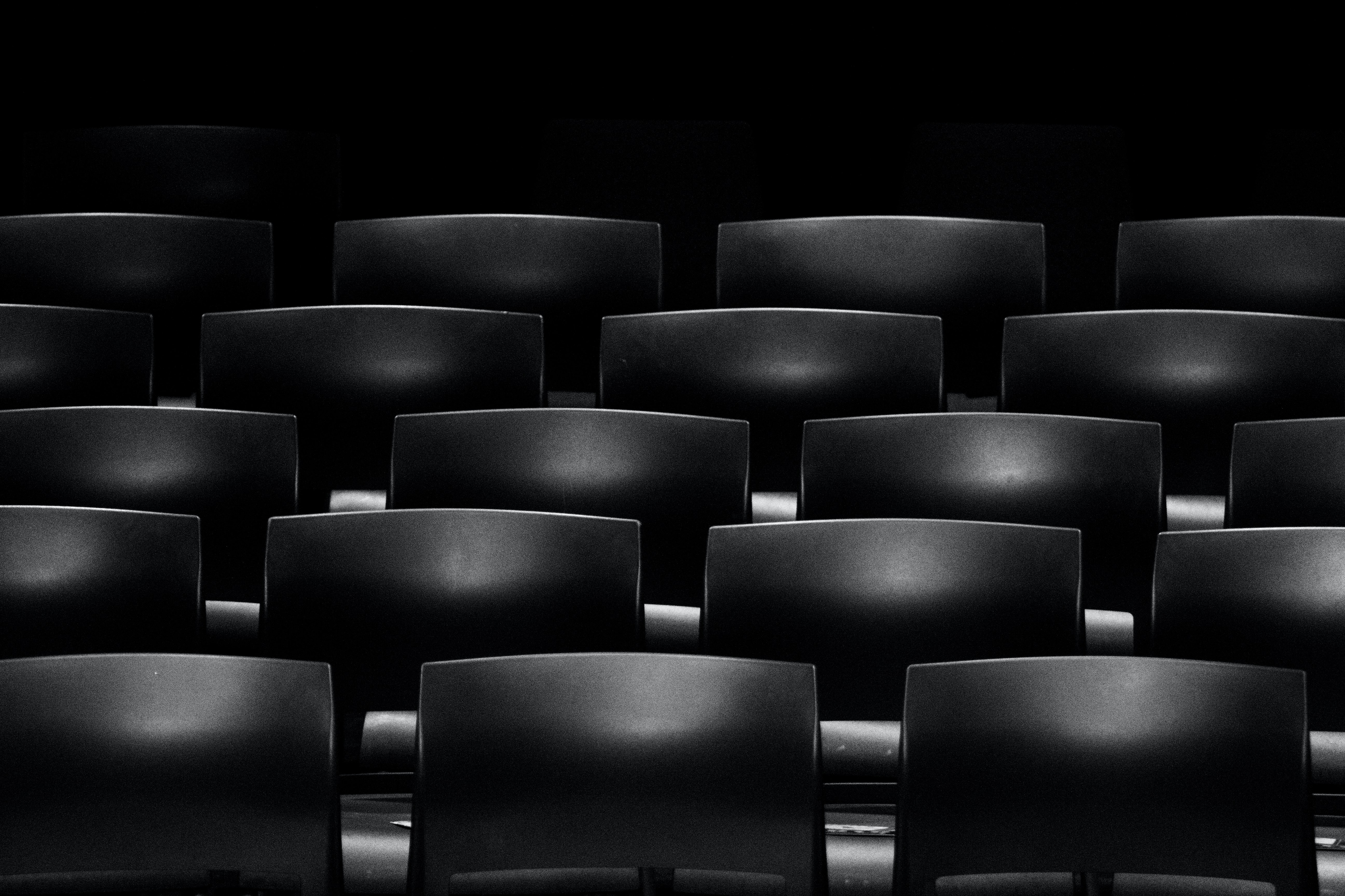 A dim shot of rows of empty seats in a movie theater