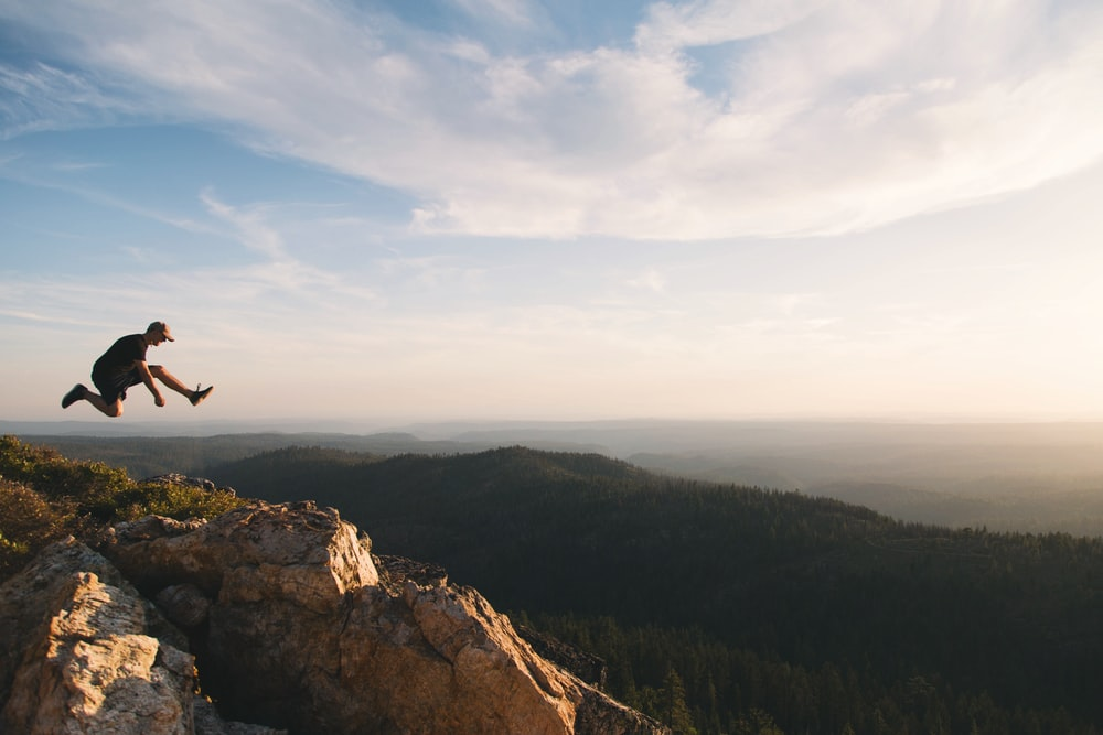 man jumping on brown rock mountain during daytime