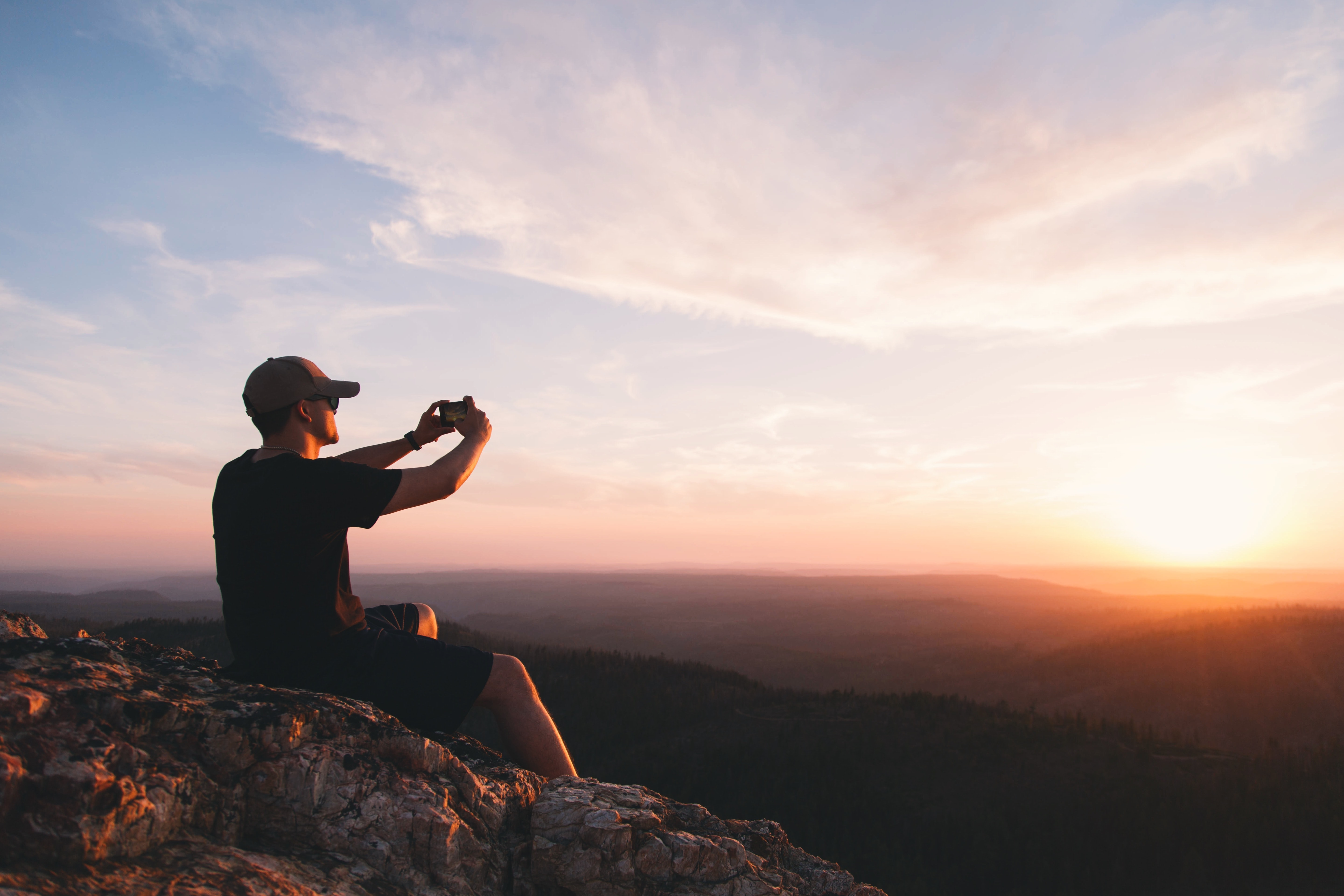 man sitting on mountain cliff taking picture