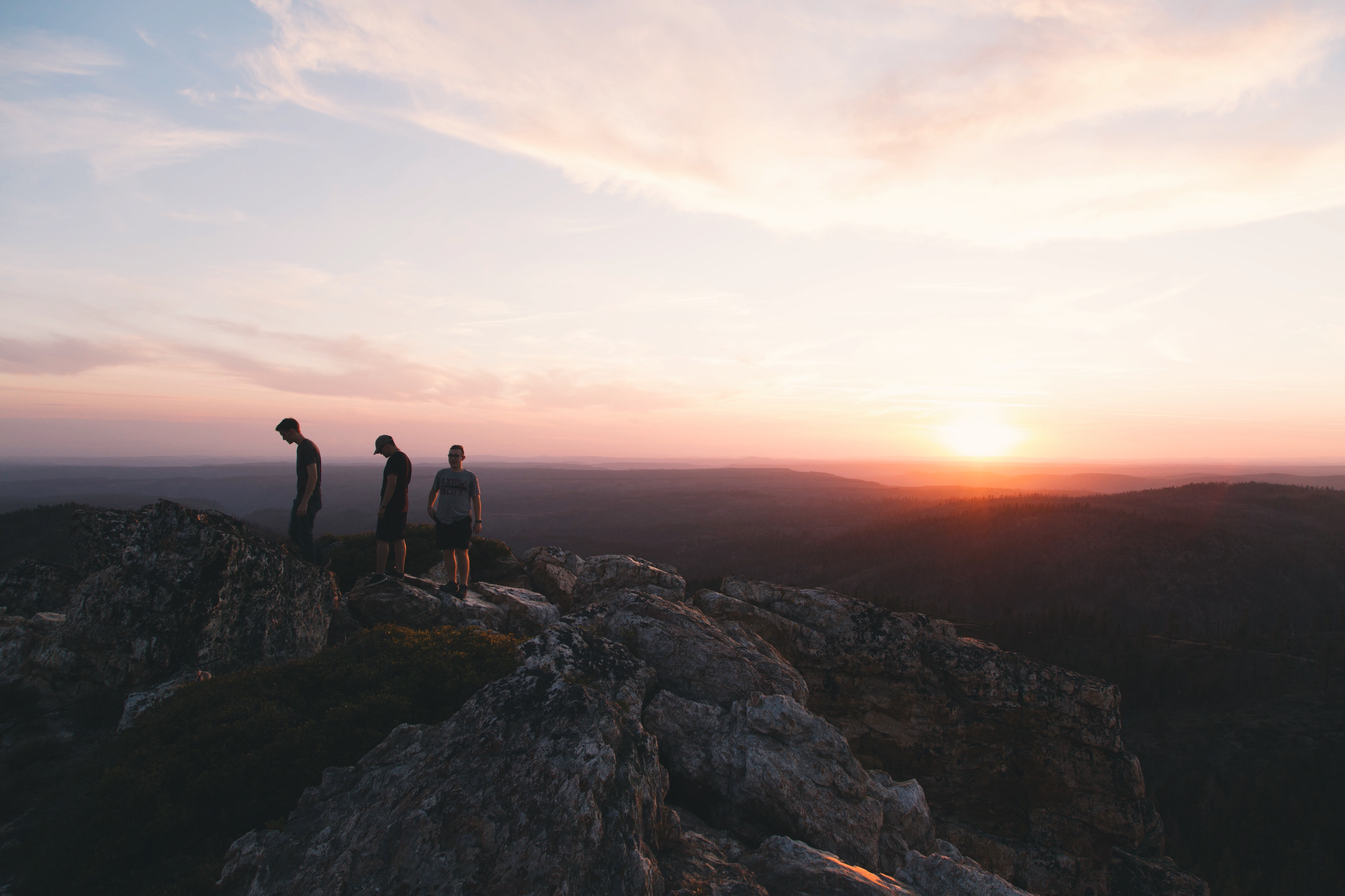 three person standing on mountain during daytime