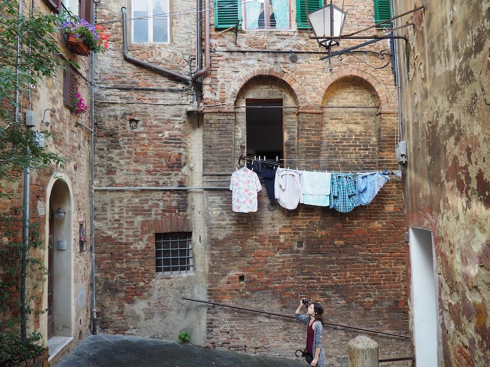 woman taking photo of apartment-type house