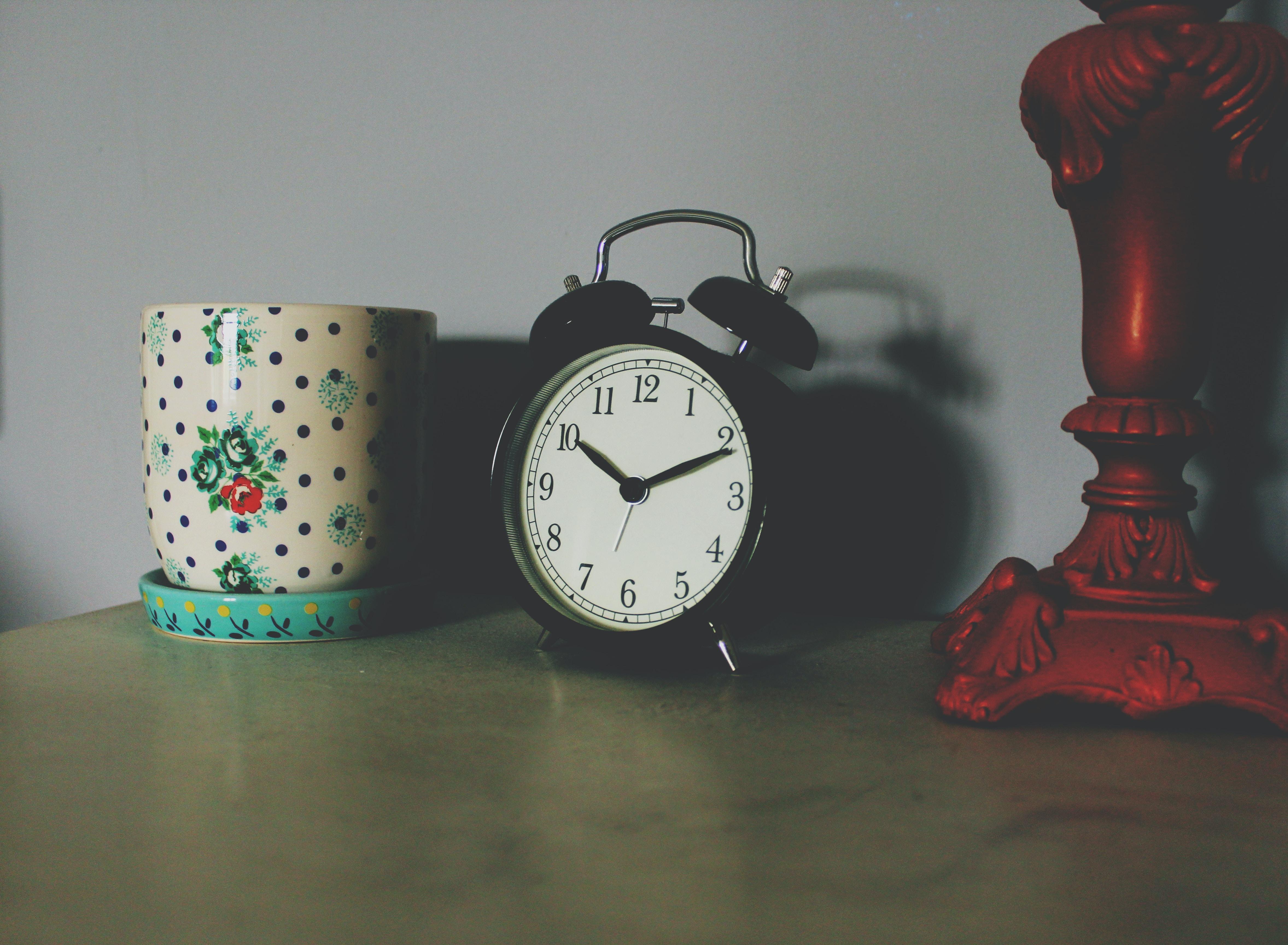 black table clock beside ceramic vase