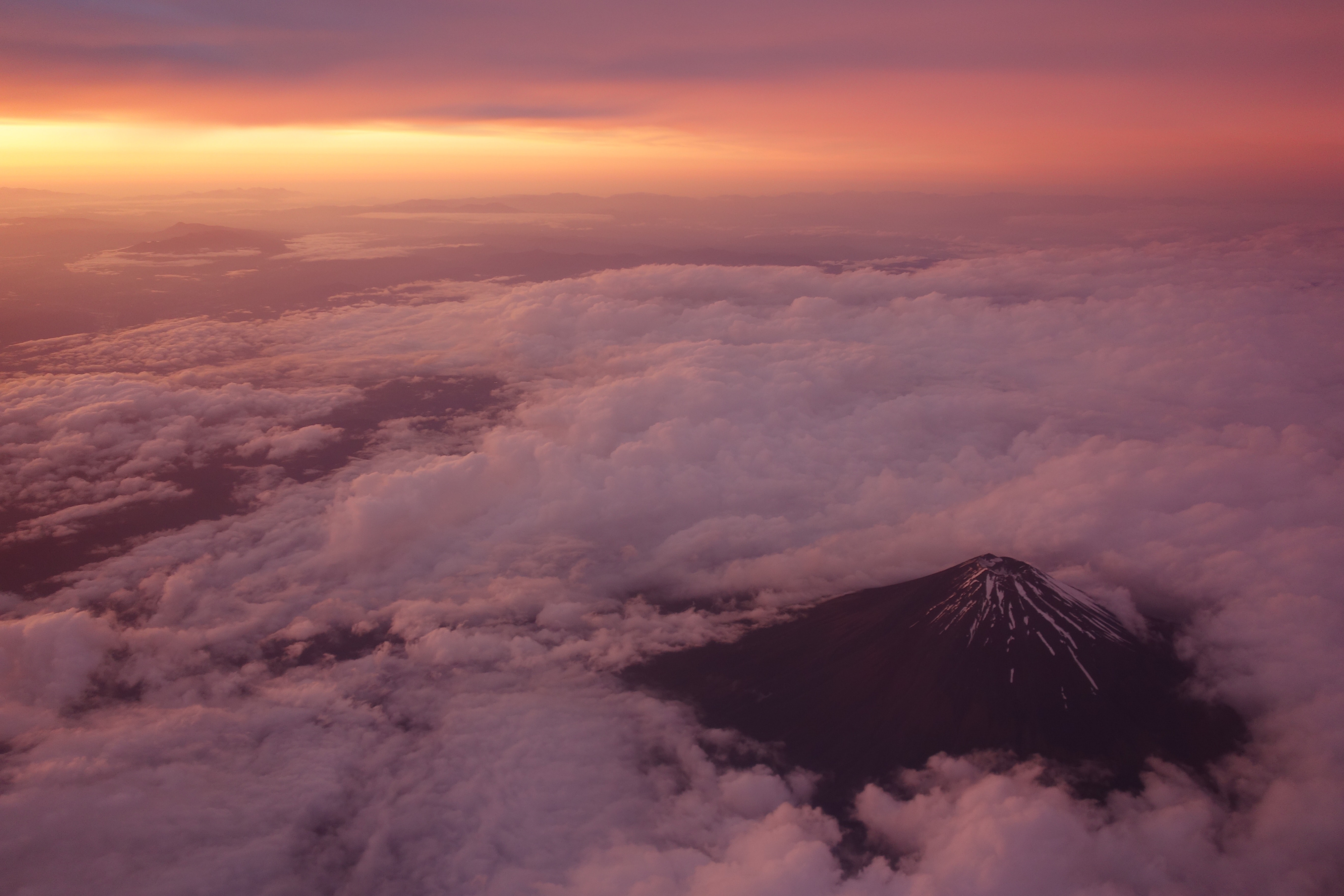 black mountain surrounded with clouds at golden hour