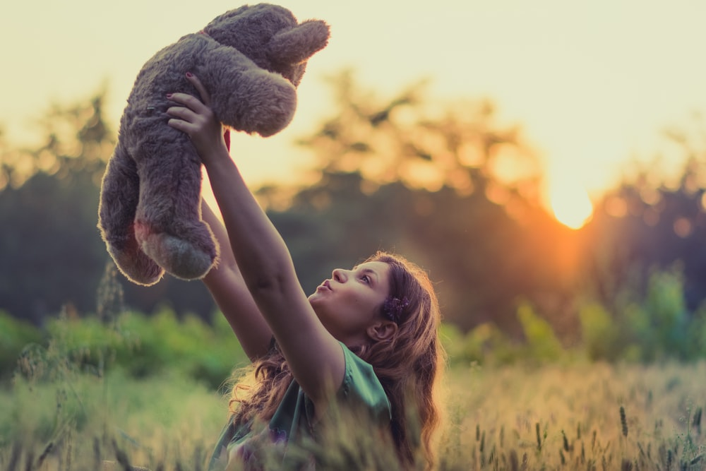 woman lifting brown bear plush toy