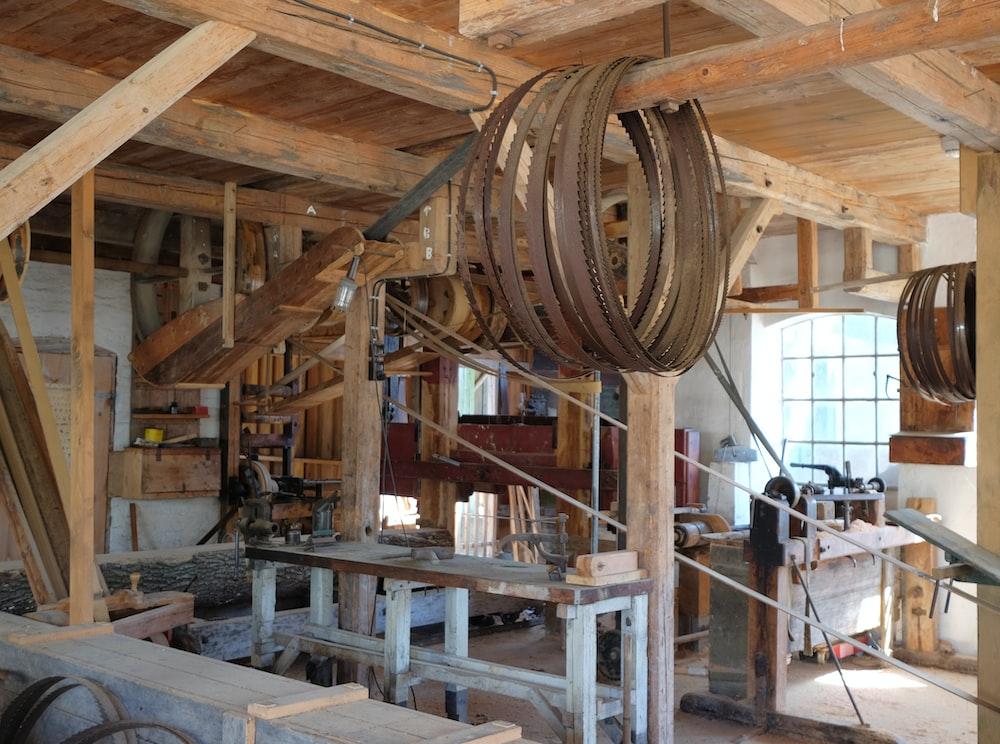 brown belts hanged in brown wooden post inside building