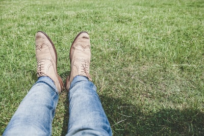 person wearing blue jeans and pair of white shoes boot zoom background