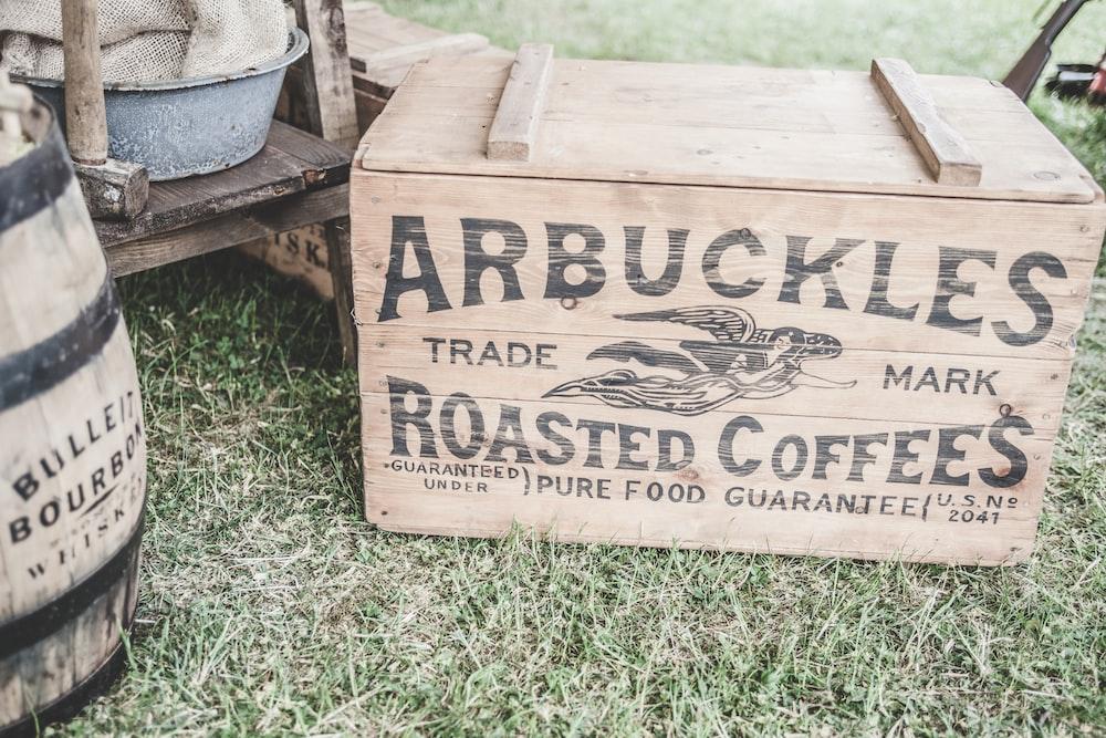 brown wooden storage box beside barrel on grass field