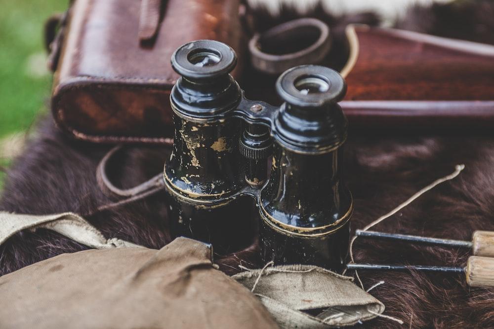 black binoculars beside bag