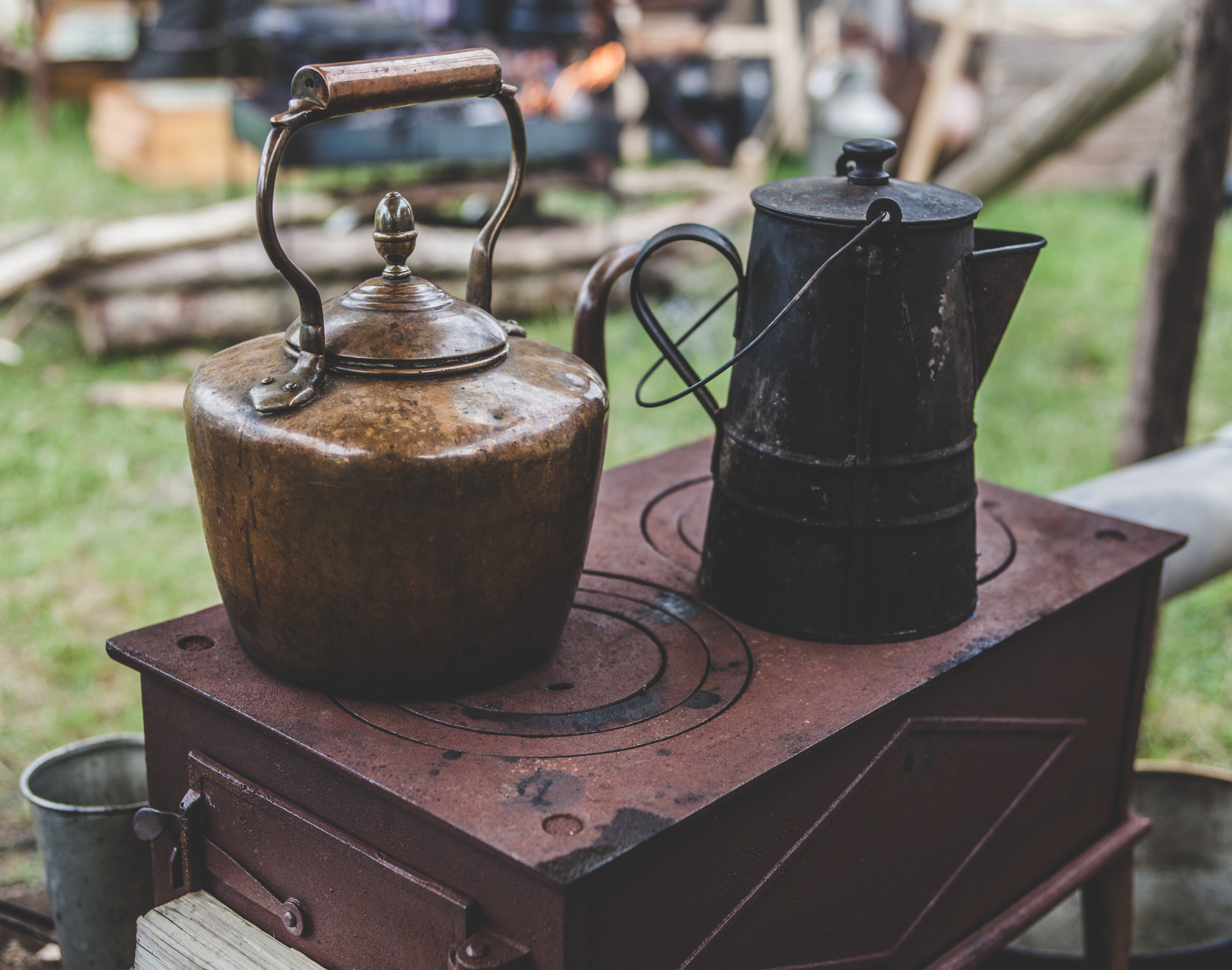 Rustic kettles on top of an antique stove outdoors