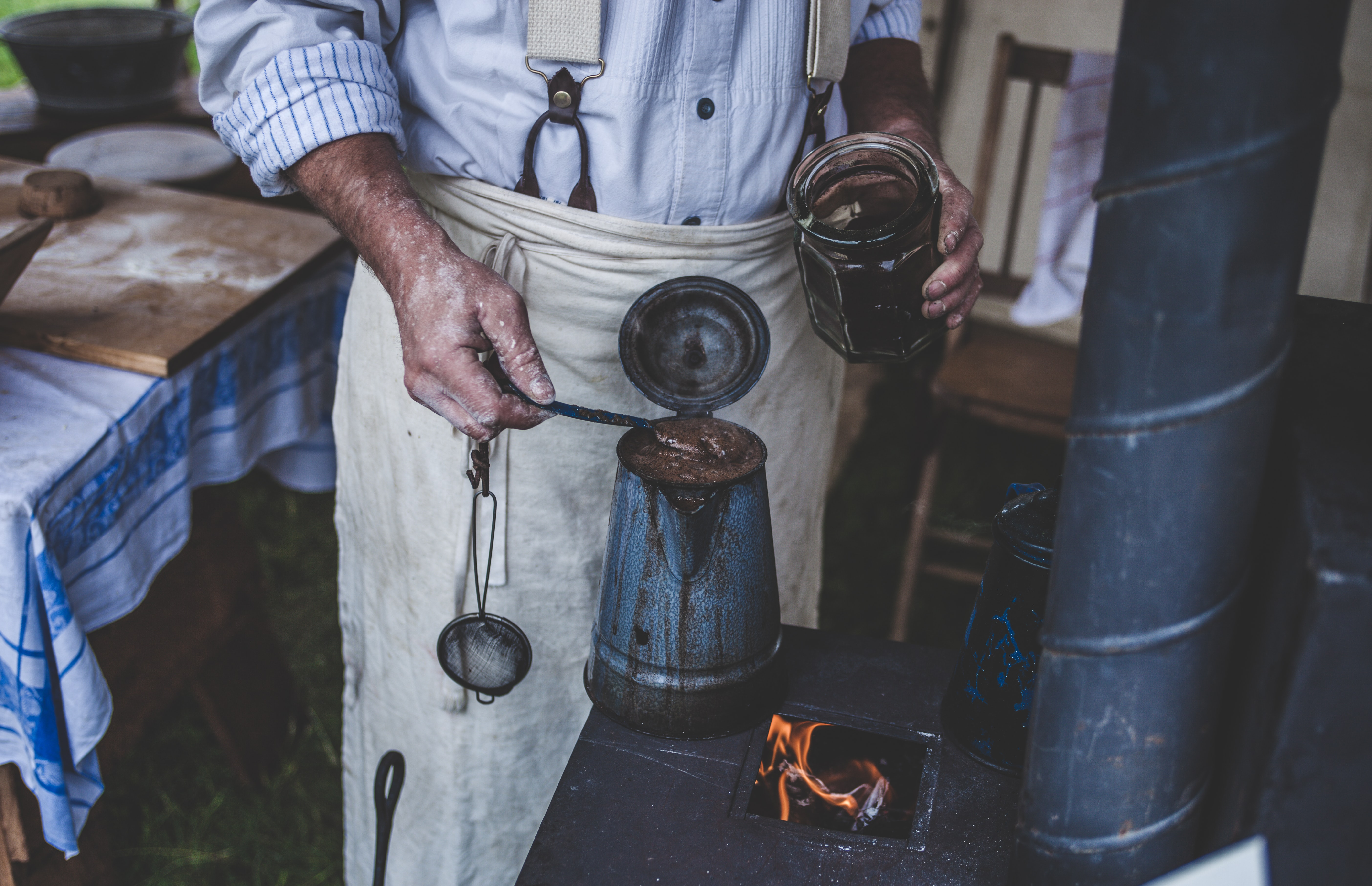 A person making coffee in an old pot on a wood-burning stove