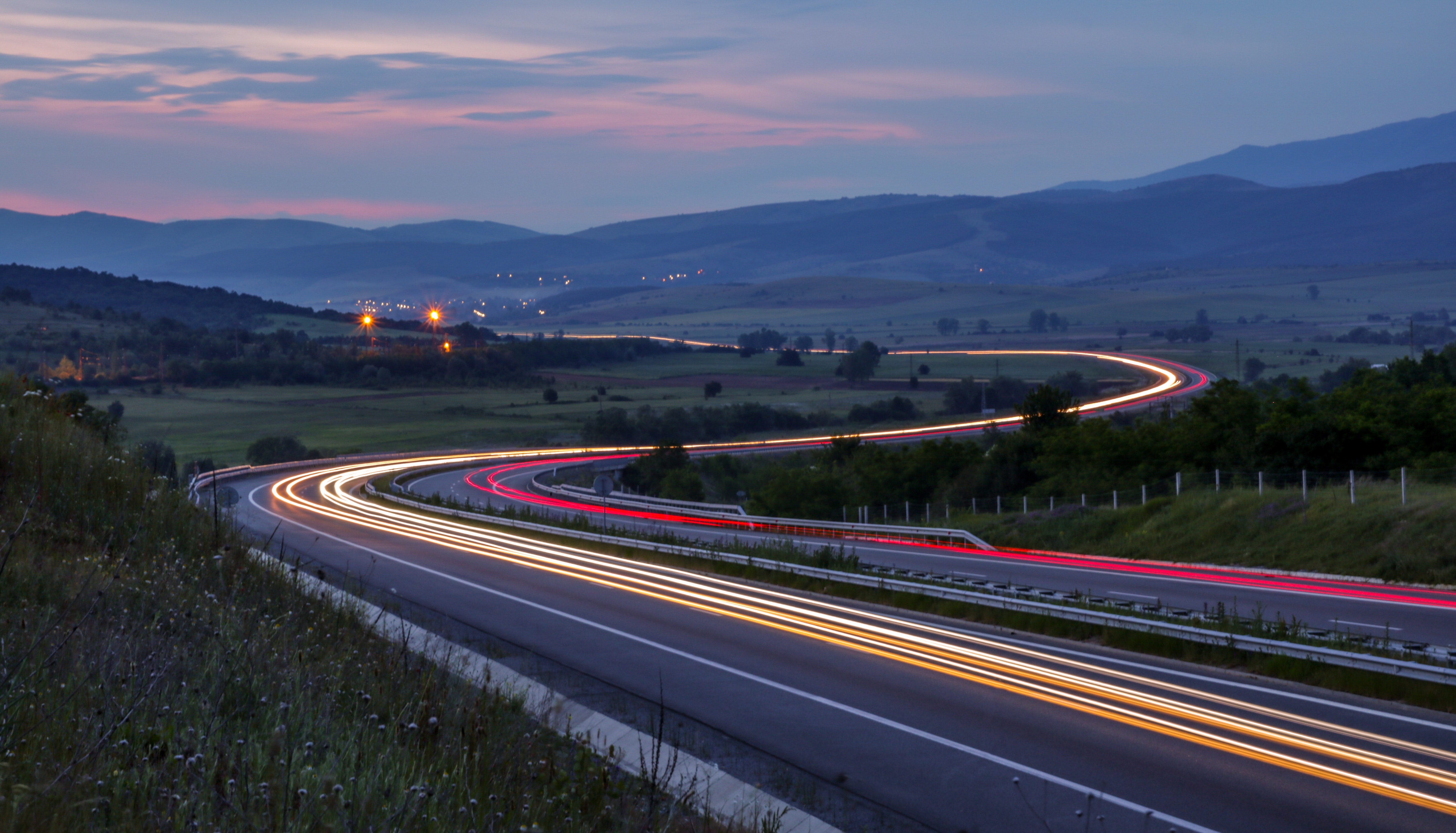 Car light trails on a winding highway in the green valley