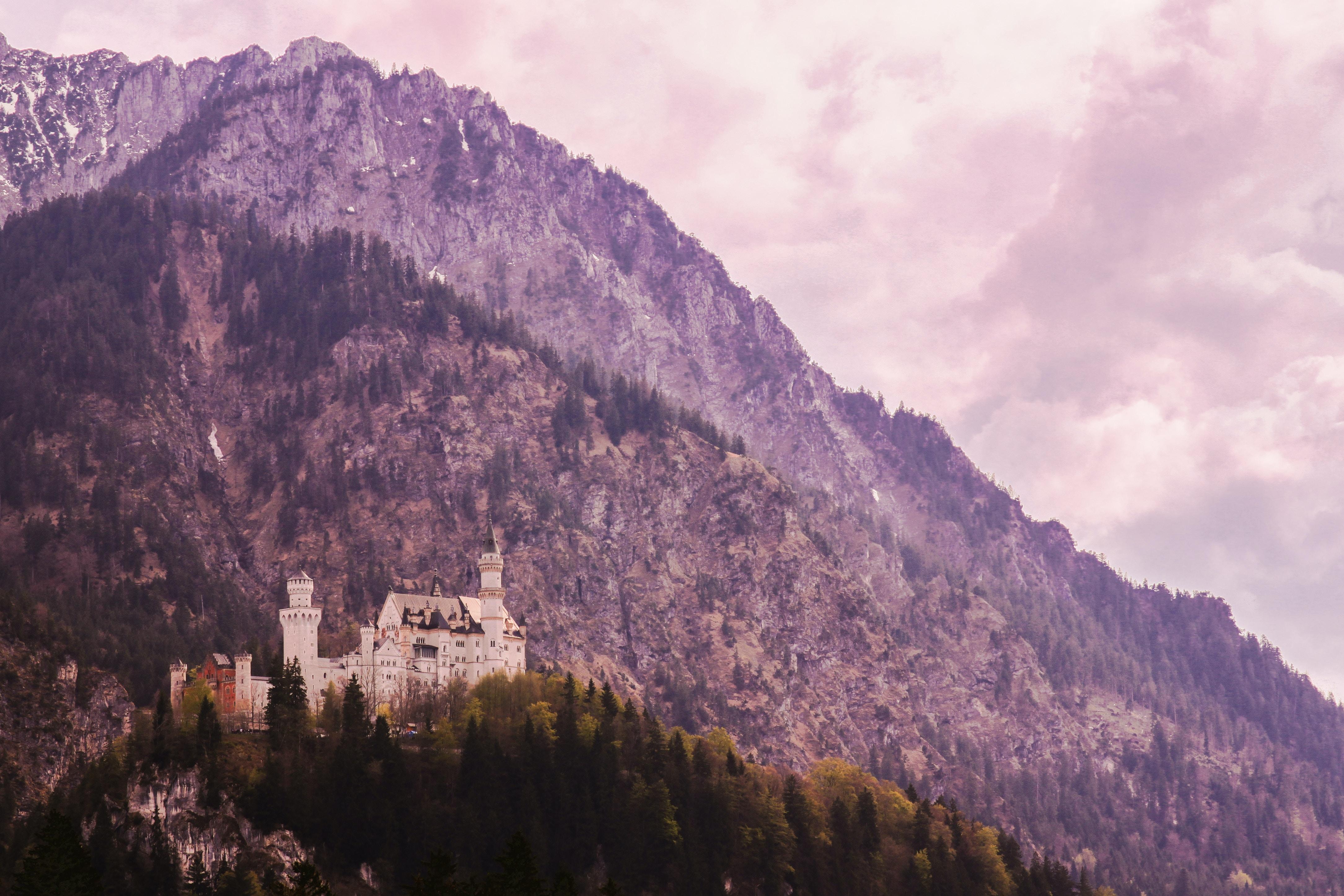 Tall purple-hued mountain towering over Neuschwanstein Castle