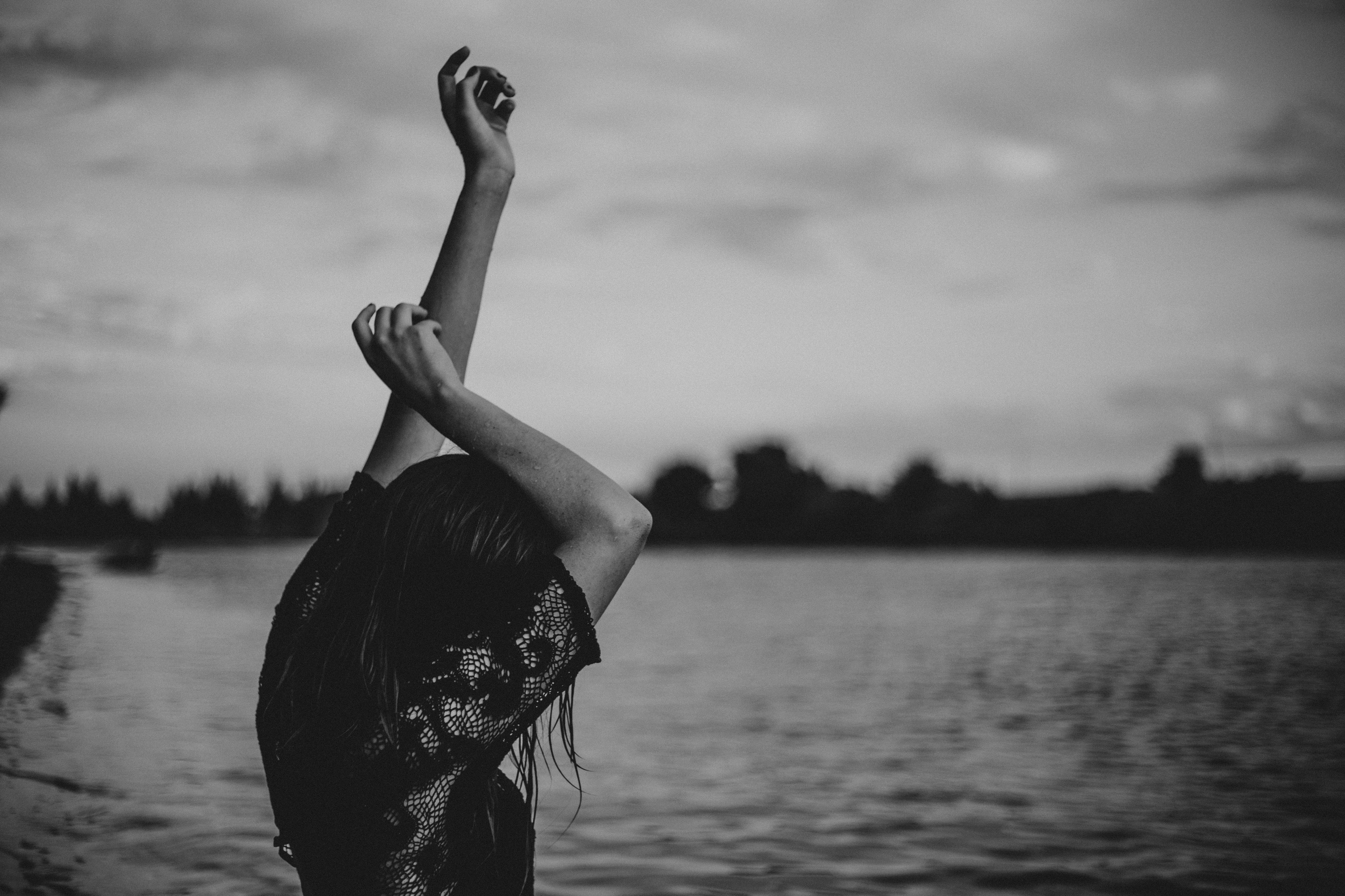 grayscale photo of woman stretching body front of body of water