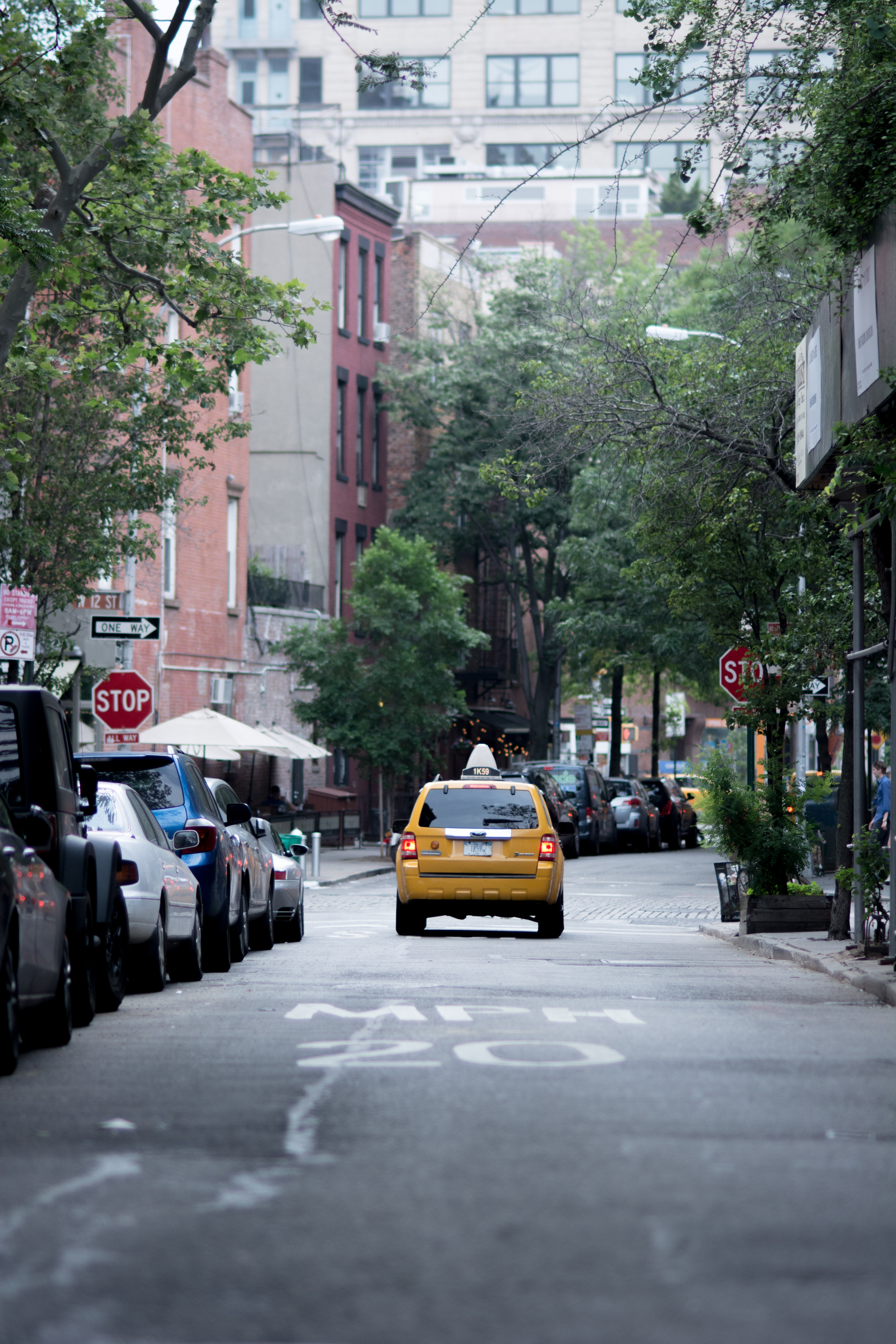 A yellow taxi cab in front of a stop sign on a New York side street