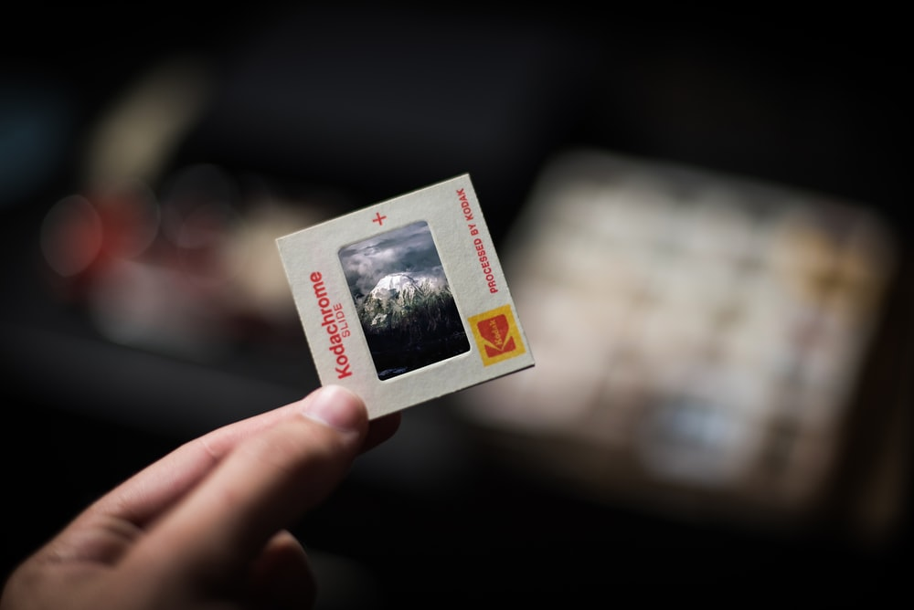 person holding white Kodachrome box